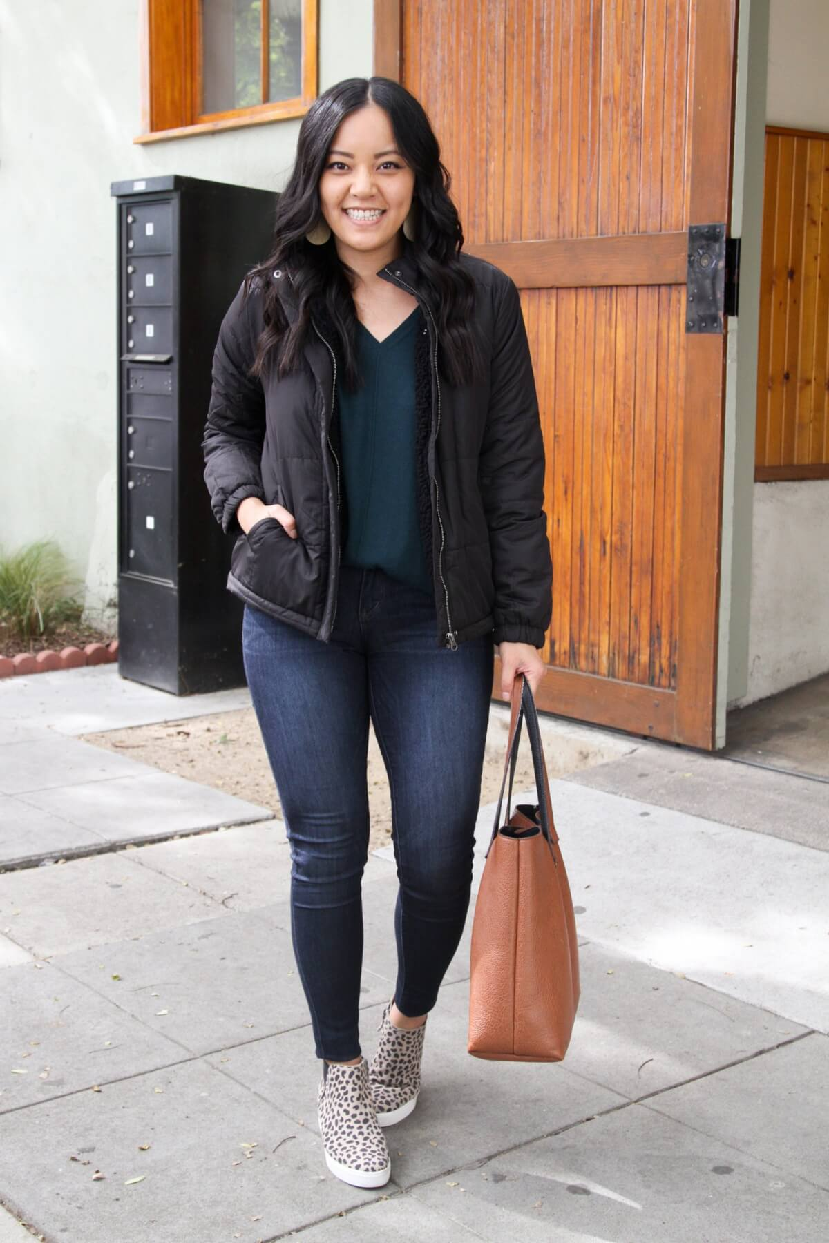 Fall Skinny Jeans Outfit: black puffer jacket + dark green v-neck sweater + leopard wedge sneakers + skinny jeans + gold leather earrings + cognac tote
