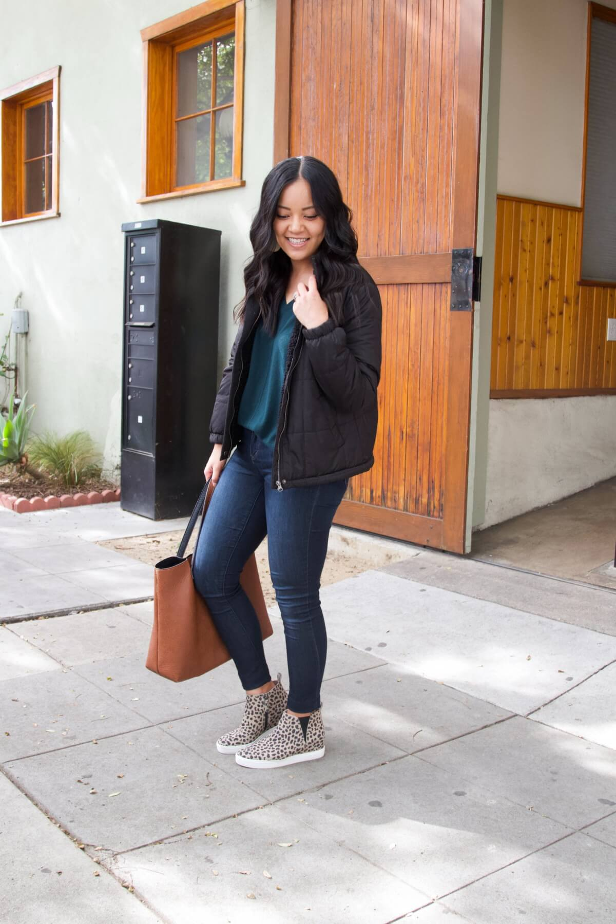 Fall Skinny Jeans Outfit: dark green v-neck sweater + black puffer jacket + skinny jeans + leopard wedge sneakers + cognac tote + gold leather earrings