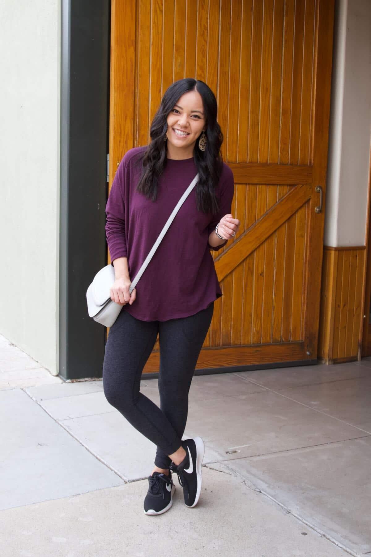 Athleisure Outfit: long sleeve purple top + black pocket leggings + black sneakers + grey crossbody bag + leather leopard print earrings