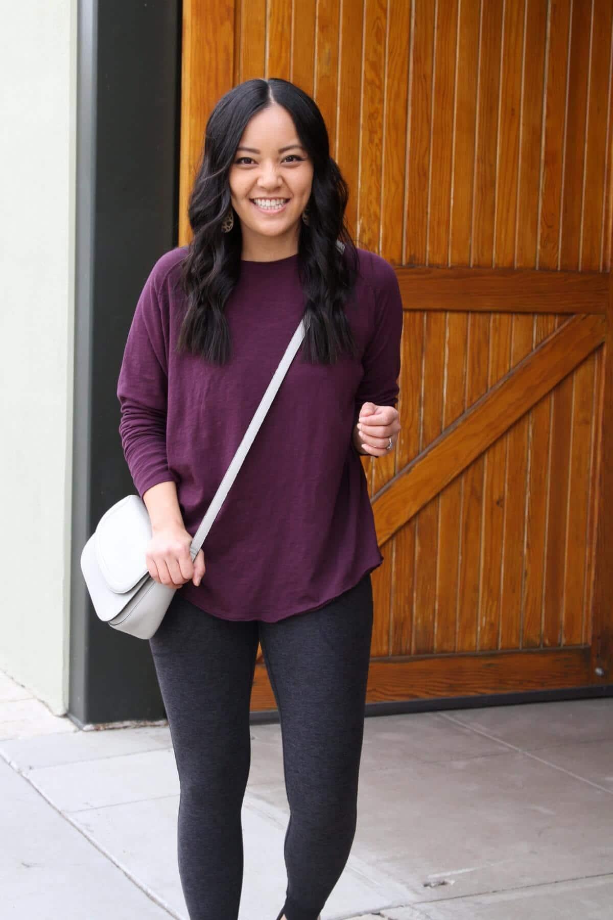 Athleisure Outfit: long sleeve purple top + black pocket leggings + grey crossbody bag + black sneakers + leather leopard print earrings