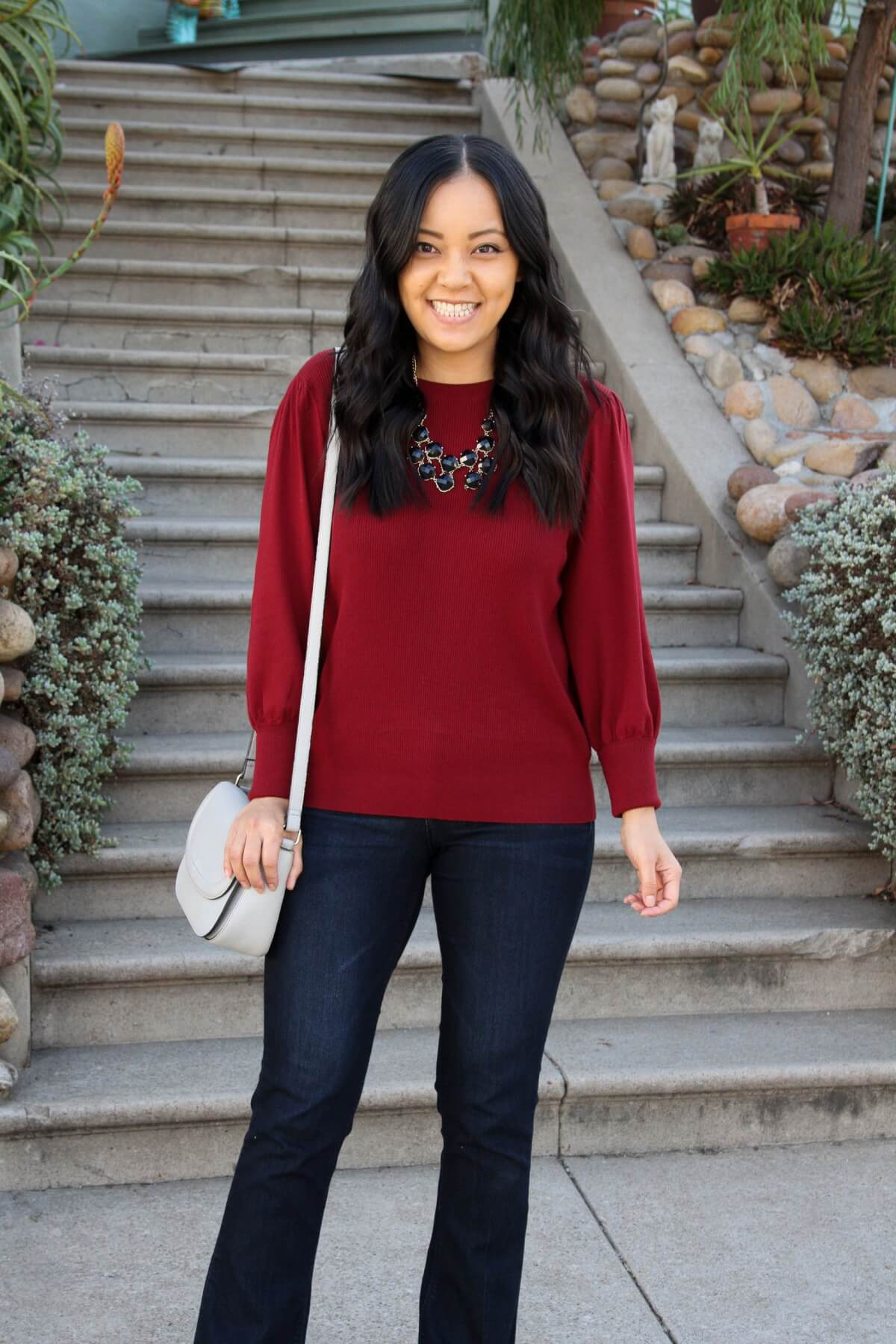 Fall Bootcut Jeans Outfit: bootcut jeans + red sweater + grey crossbody bag + black statement necklace
