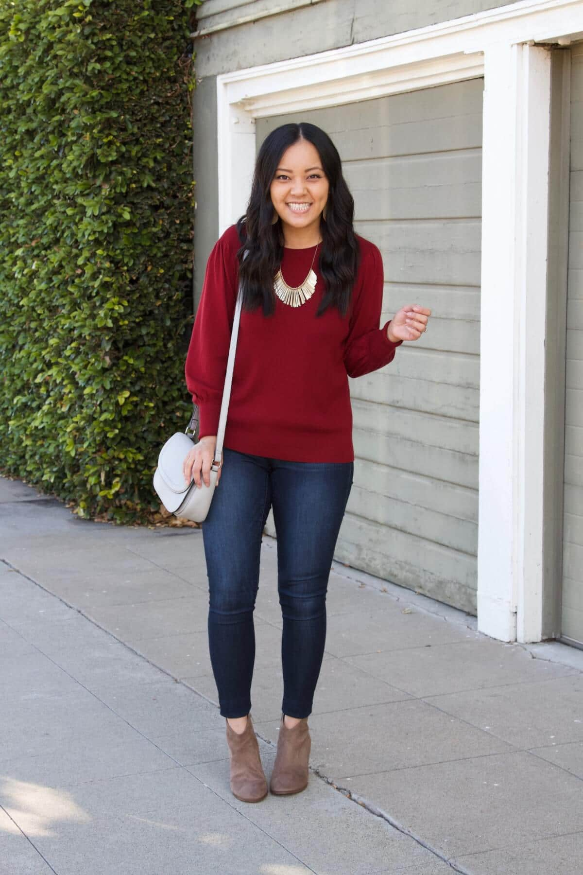 Fall Jeans Outfit: red sweater + skinny jeans + taupe suede booties + grey crossbody bag + gold fringe statement necklace + tan leather earrings