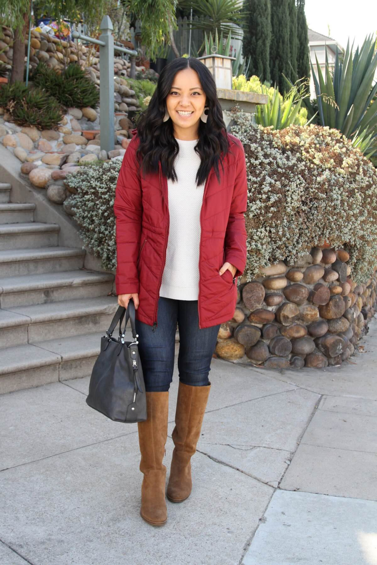 Casual Winter Outfit: white sweater + red puffer jacket + skinny jeans + tan suede boots + dark grey bag + cream leather earrings