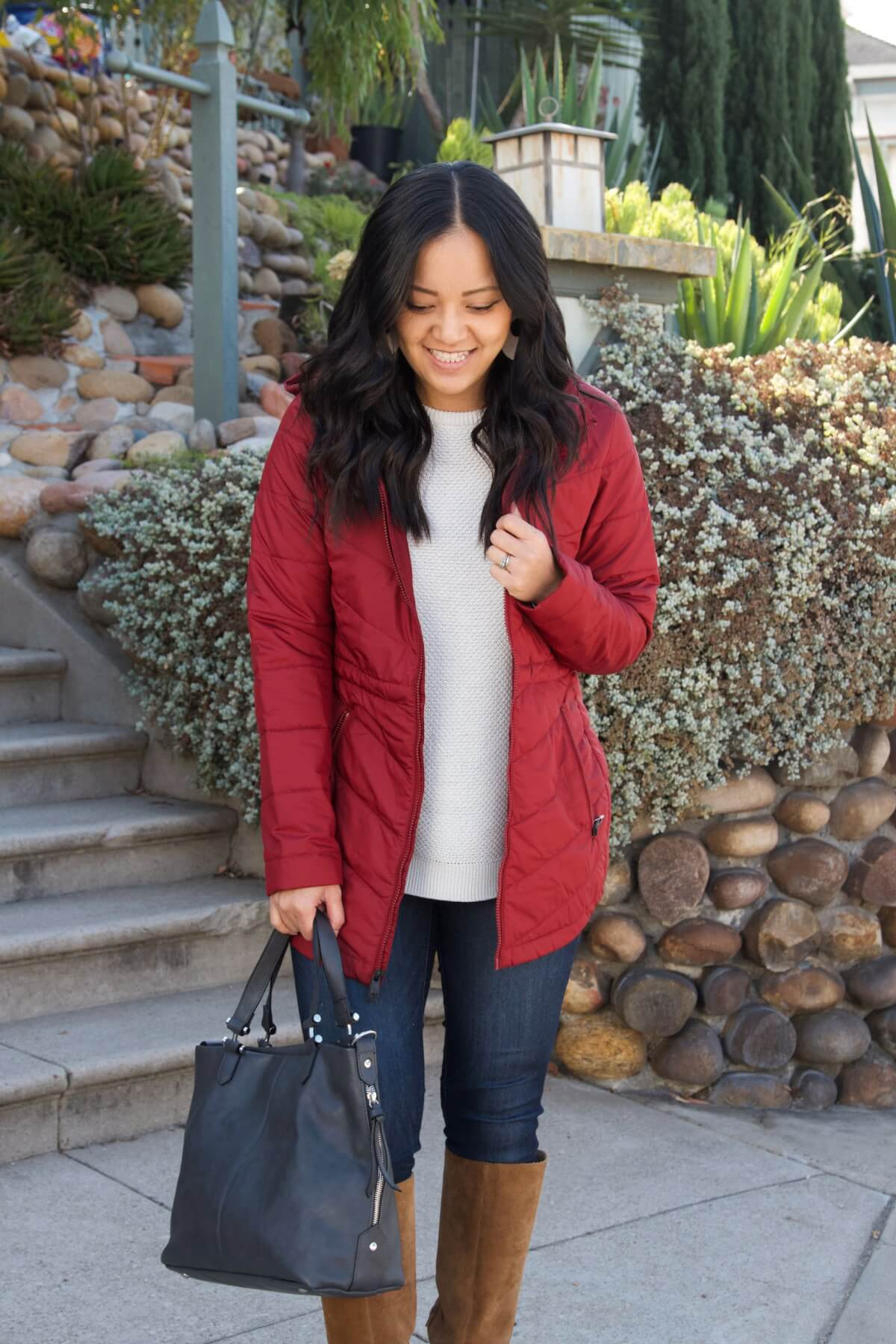 Casual Winter Outfit: white sweater + red puffer jacket + tan suede boots + skinny jeans + dark grey bag + cream leather earrings