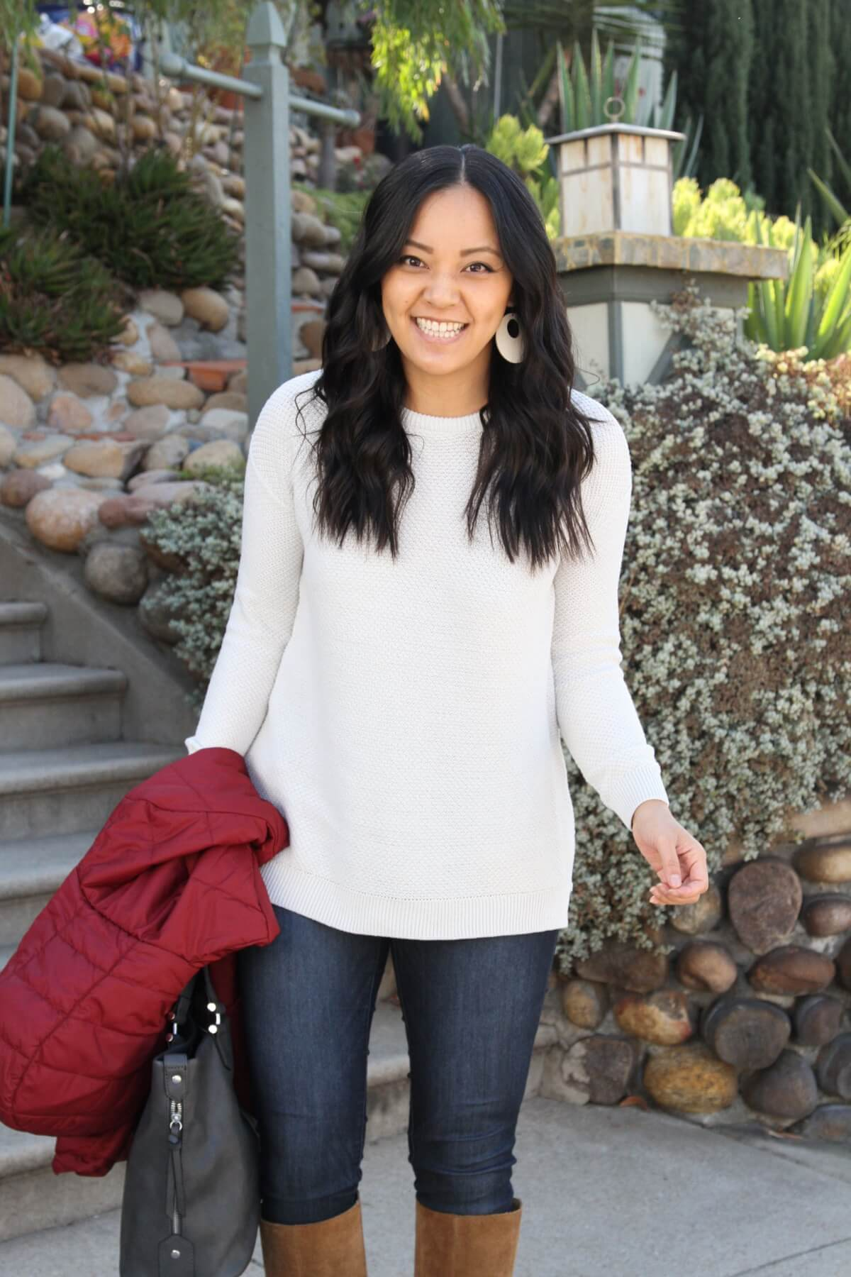 Casual Winter Outfit: red puffer jacket + white sweater + skinny jeans + tan suede boots + cream leather earrings + dark grey bag