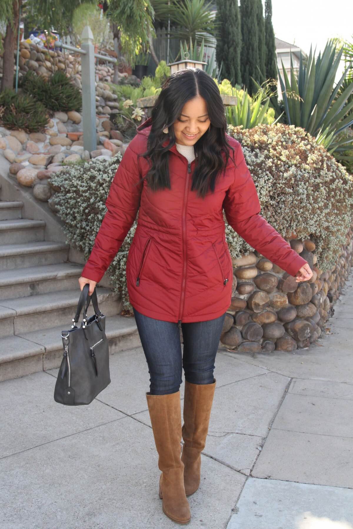 Casual Winter Outfit: red puffer jacket + white sweater + tan suede boots + skinny jeans + cream leather earrings + dark grey bag