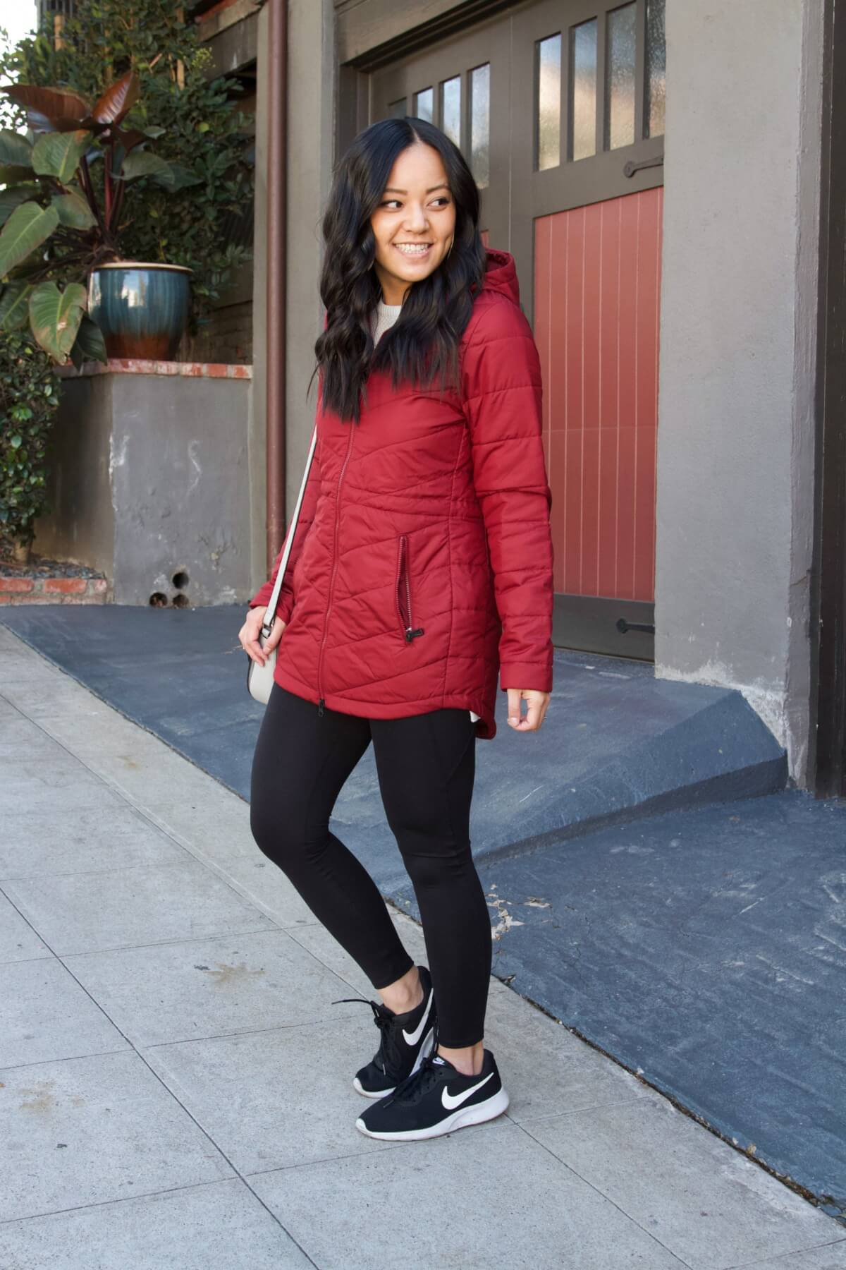 Casual Winter Outfit: white sweater + red puffer jacket + black sneakers + black leggings + grey crossbody bag + cream leather earrings