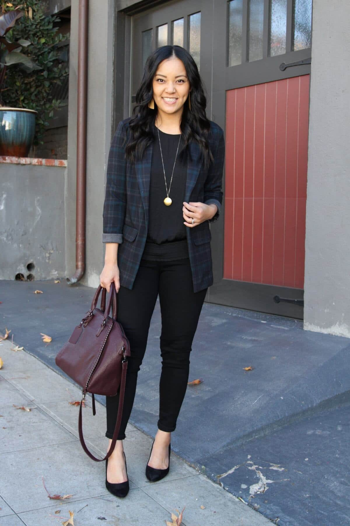 Business Casual Outfit: black blouse + black plaid blazer + black skinny pants + black suede heels + maroon bag + gold circle pendant necklace + metallic leather earrings