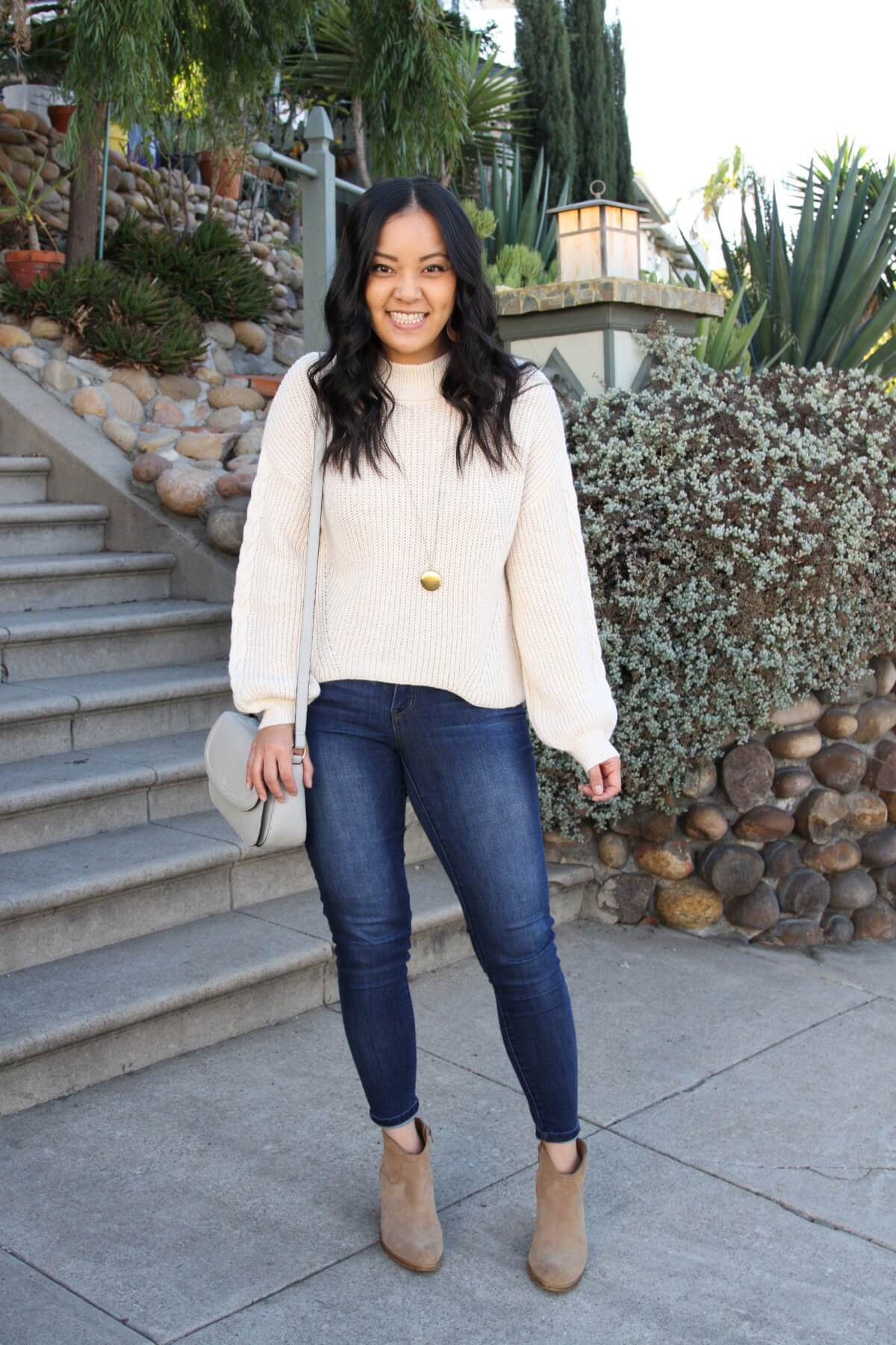 Fall Sweater Outfit: skinny jeans + cream dolman sleeve sweater + gold circle pendant necklace + taupe suede booties