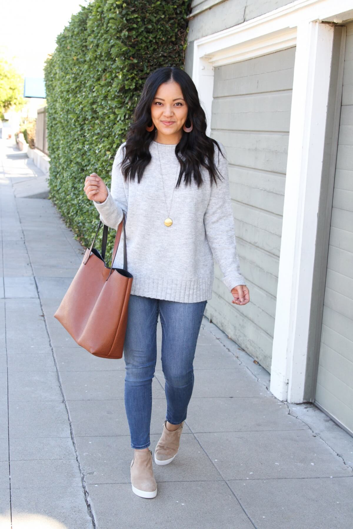 Fall Sweater Outfit: grey crewneck sweater + skinny jeans + taupe suede wedge sneakers + cognac tote + gold circle pendant necklace + tan leather earrings