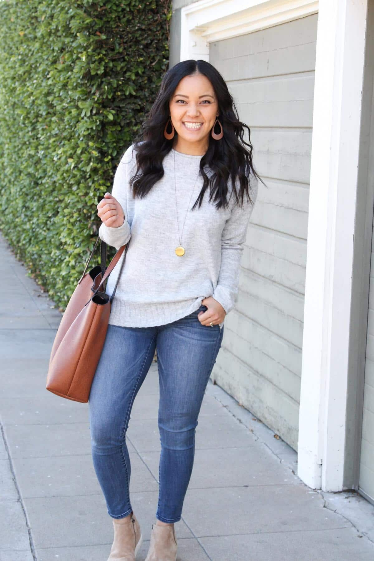 Fall Sweater Outfit: skinny jeans + grey crewneck sweater + taupe suede wedge sneakers + cognac tote + tan leather earrings + gold circle pendant necklace