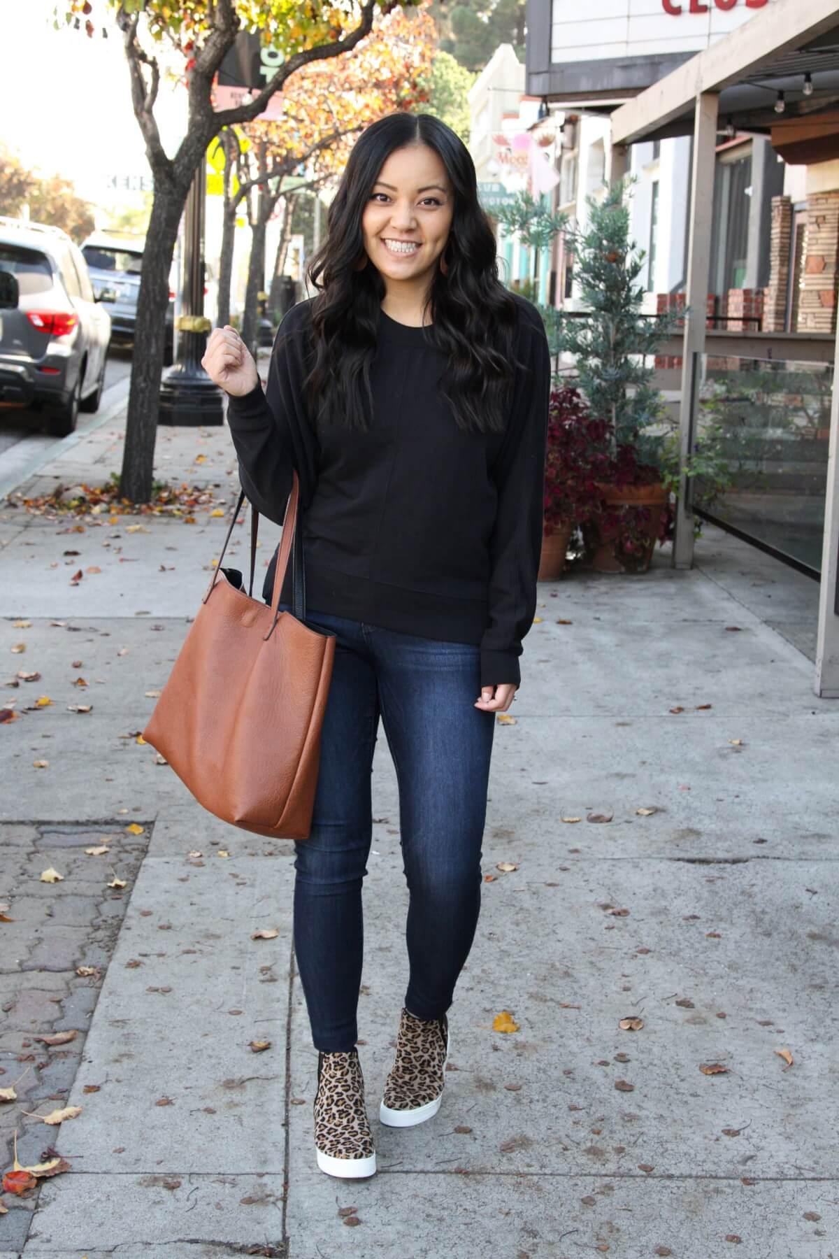 Casual Winter Outfit: black crewneck sweatshirt + skinny jeans + leopard print wedge sneakers + cognac tote + cognac leather earrings