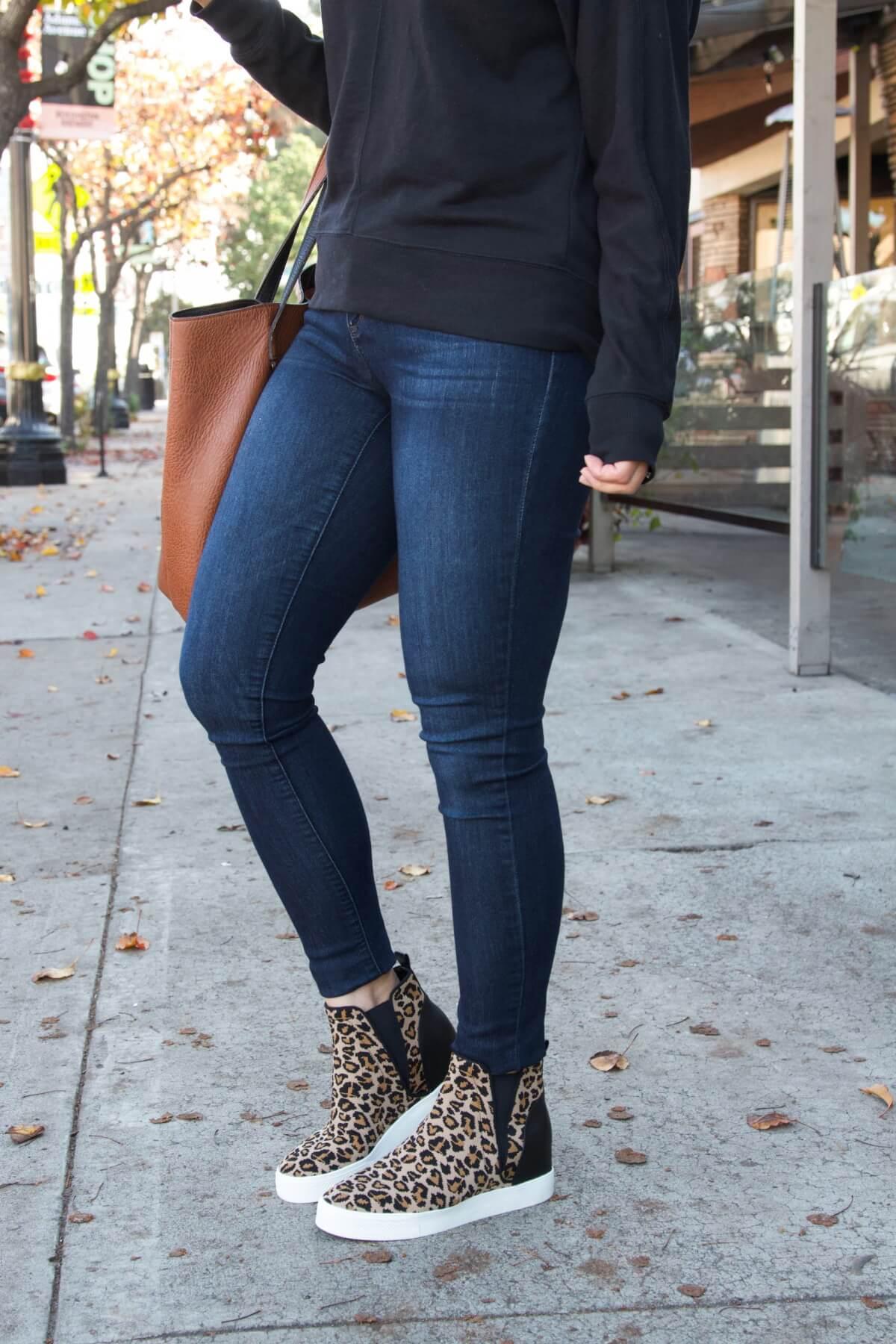 Black Sweatshirt, Skinny Jeans, Leopard Wedge Sneakers, Cognac Tote, and Tan Earrings Casual Outfit Bottom Half Side View 2
