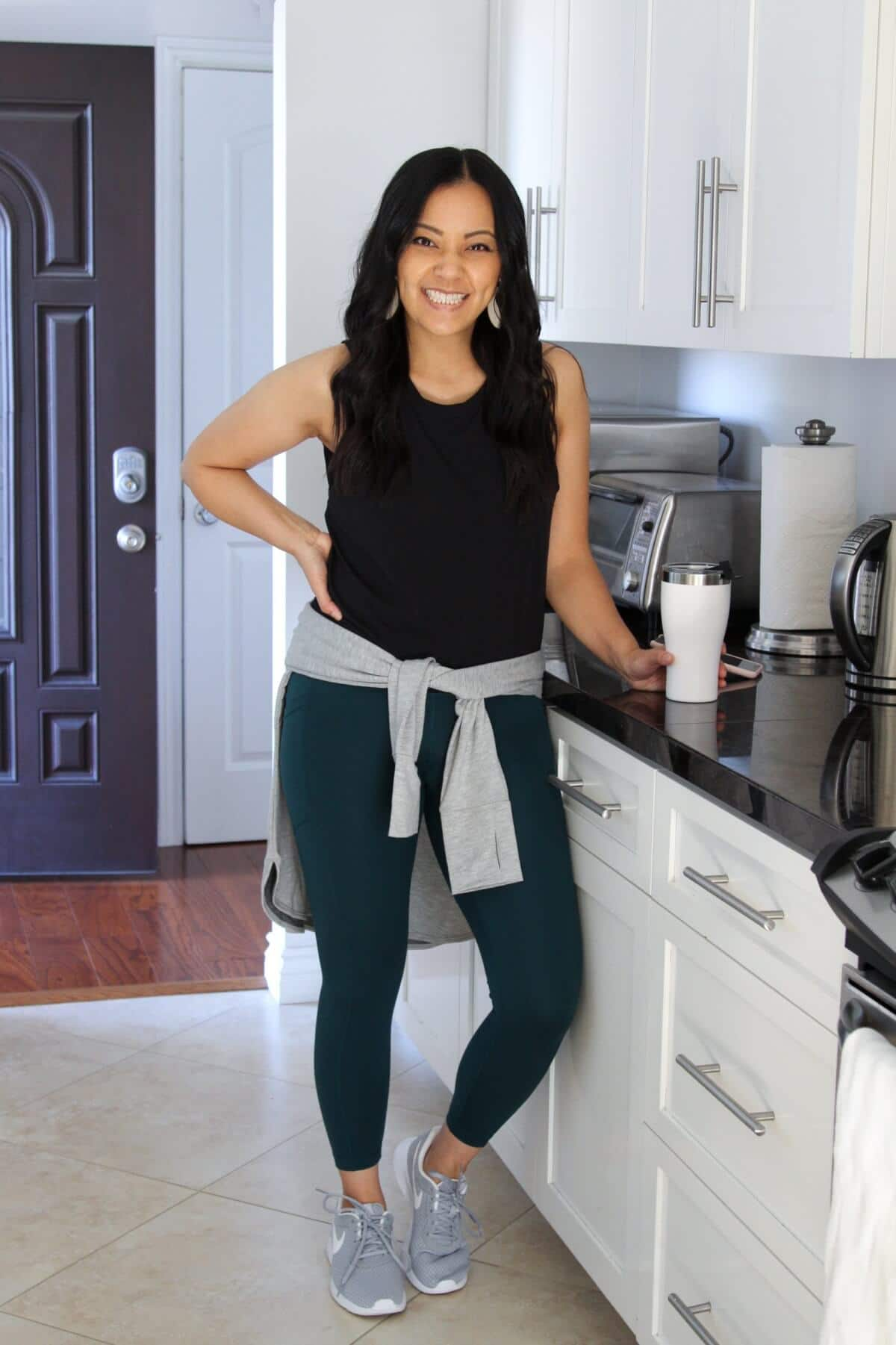 workout outfit with green leggings + black tank + grey sneakers