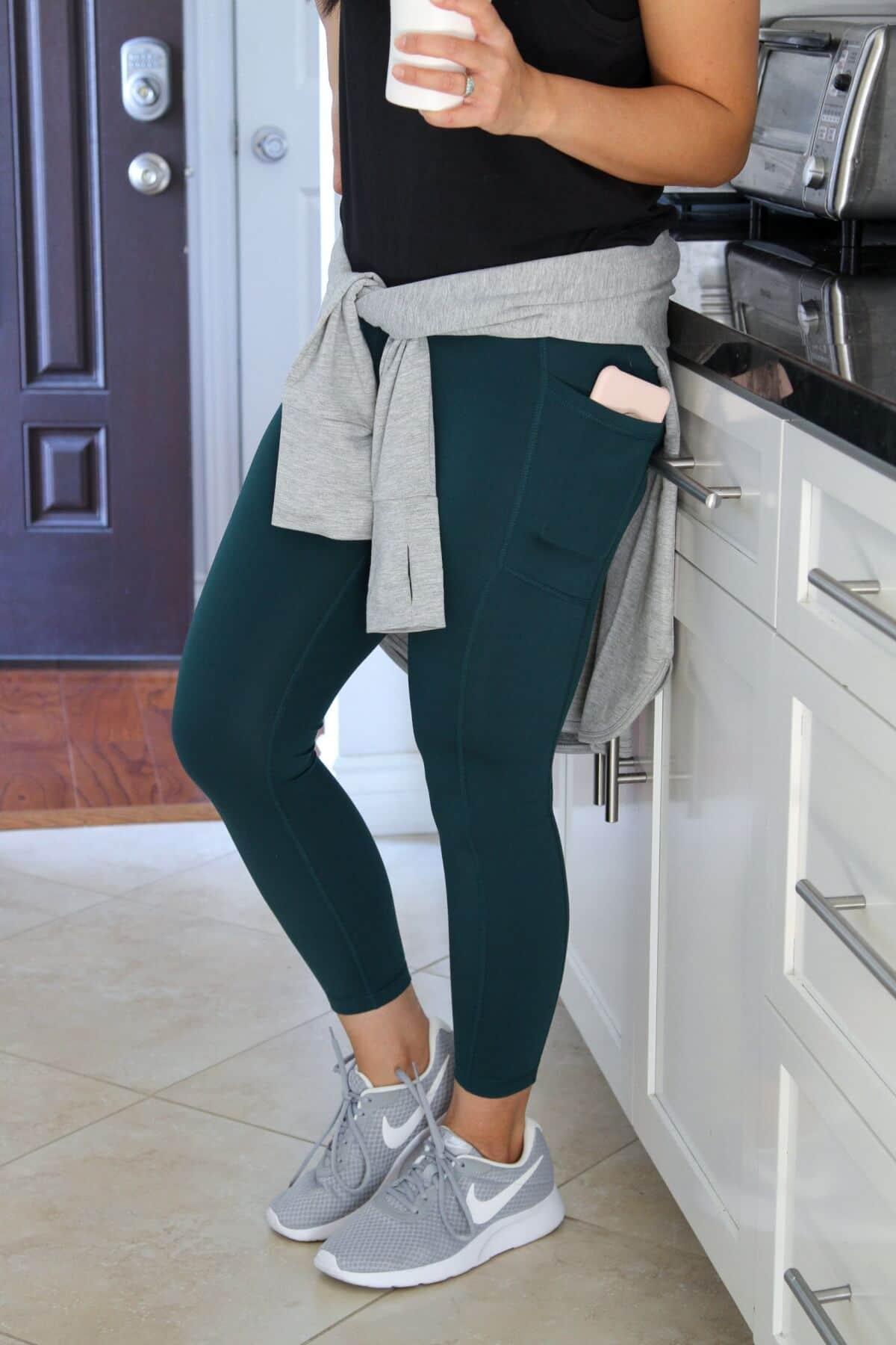 workout outfit with black tank + green leggings + grey sneakers close up