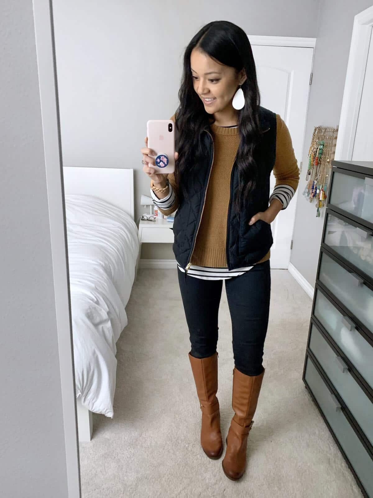 Winter Leggings Outfit: long sleeve striped tee + camel sweater + black quilted vest + black leggings + cognac leather boots + white leather earrings