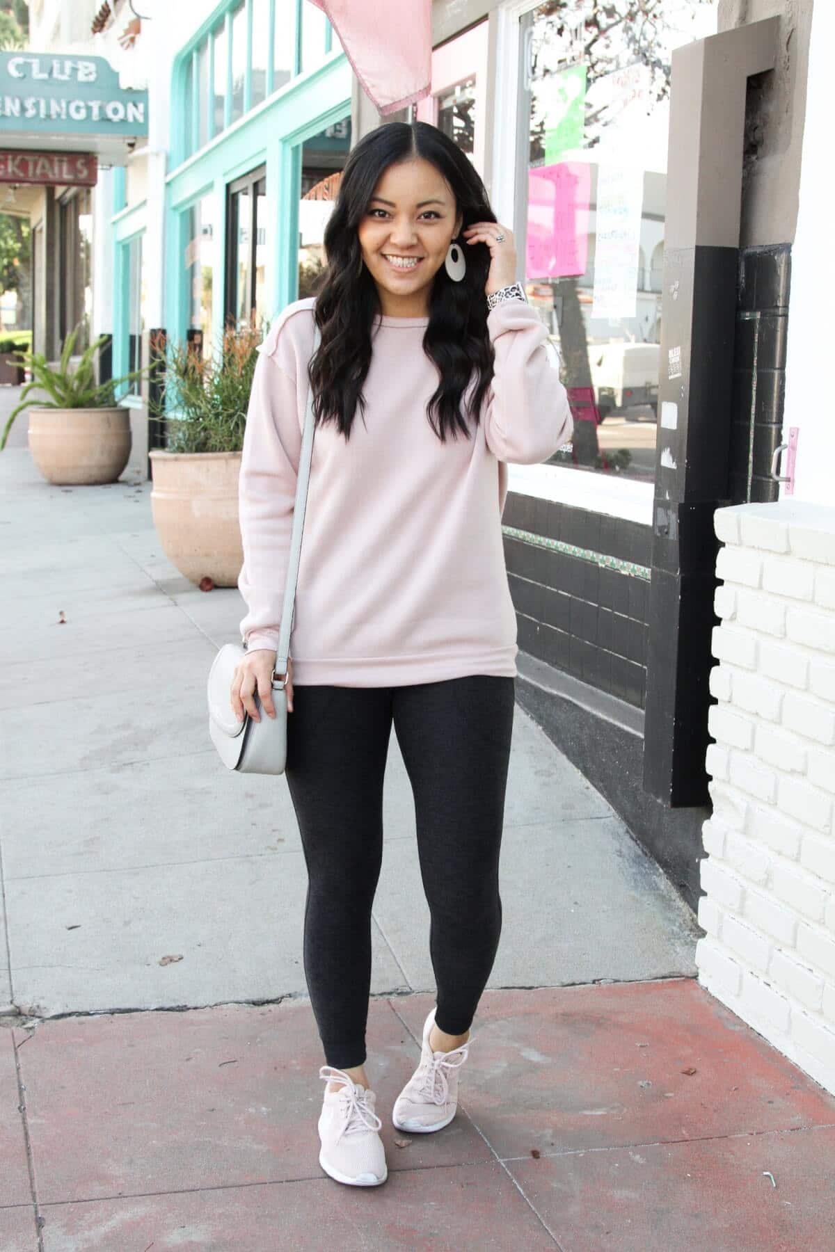Athleisure Outfit: blush sweatshirt + dark grey pocket leggings + blush sneakers + grey crossbody bag + cream leather earrings