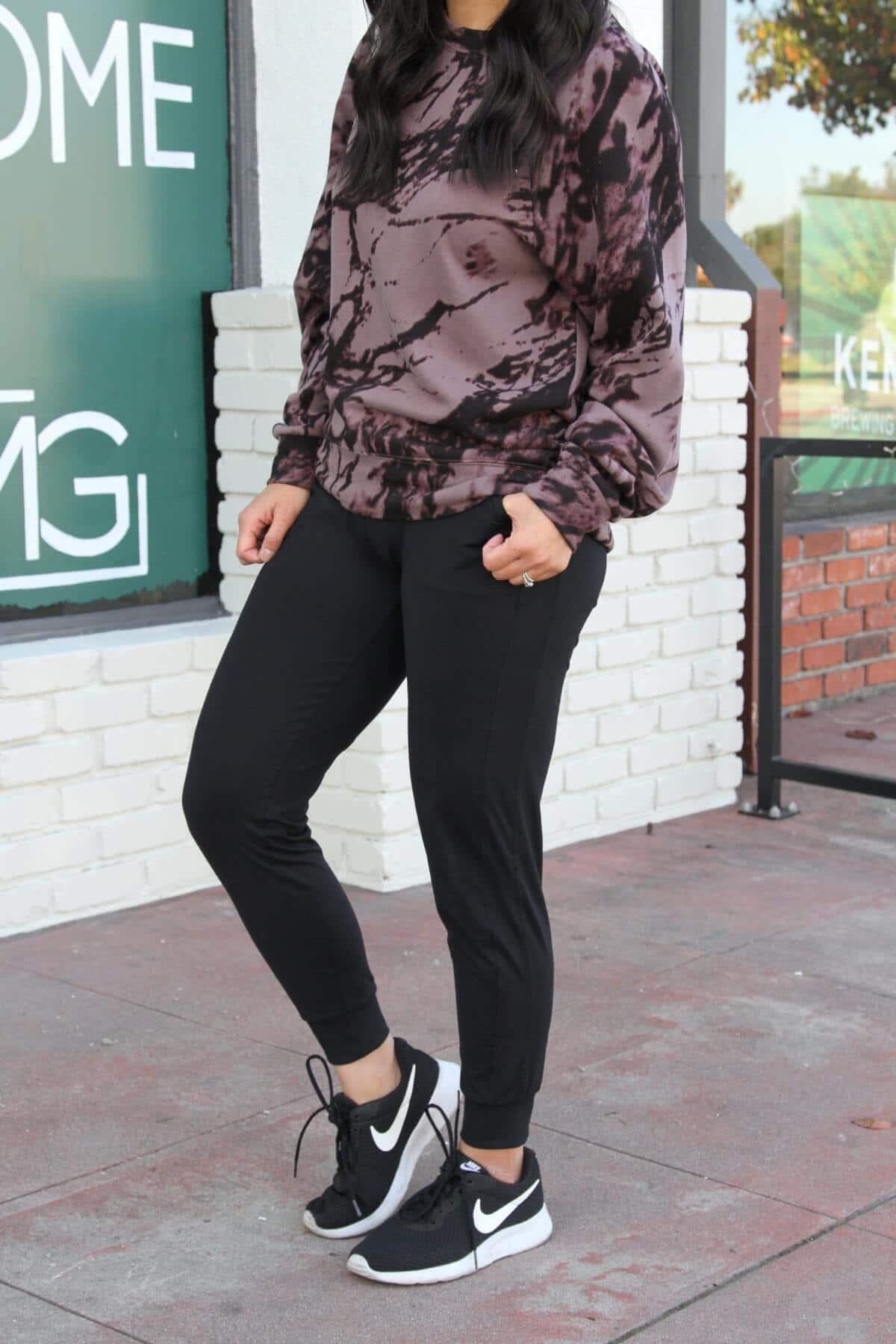 Athleisure Outfit: black joggers + purple and black splattered sweatshirt + black sneakers