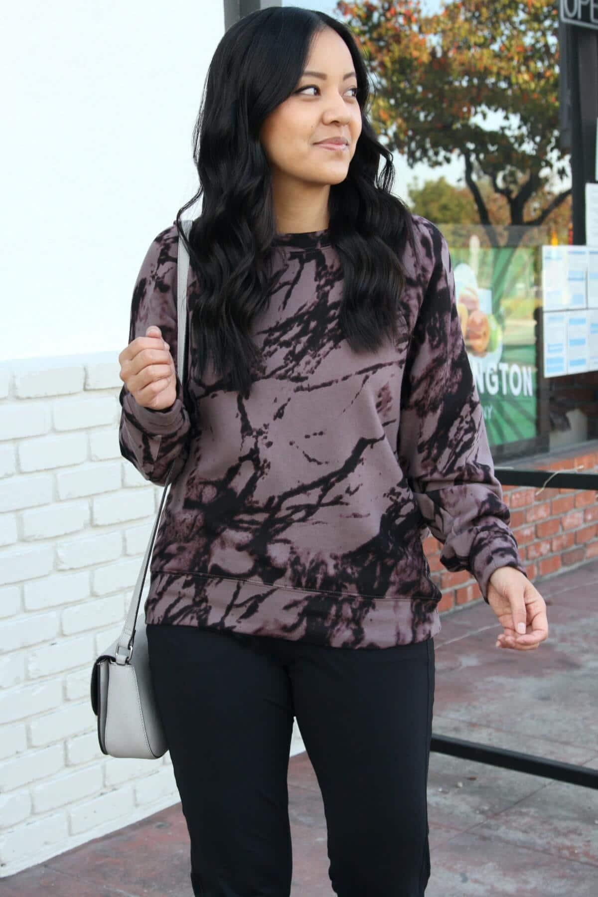 Winter Athleisure Outfit: purple and black splattered sweatshirt + black joggers + grey crossbody bag