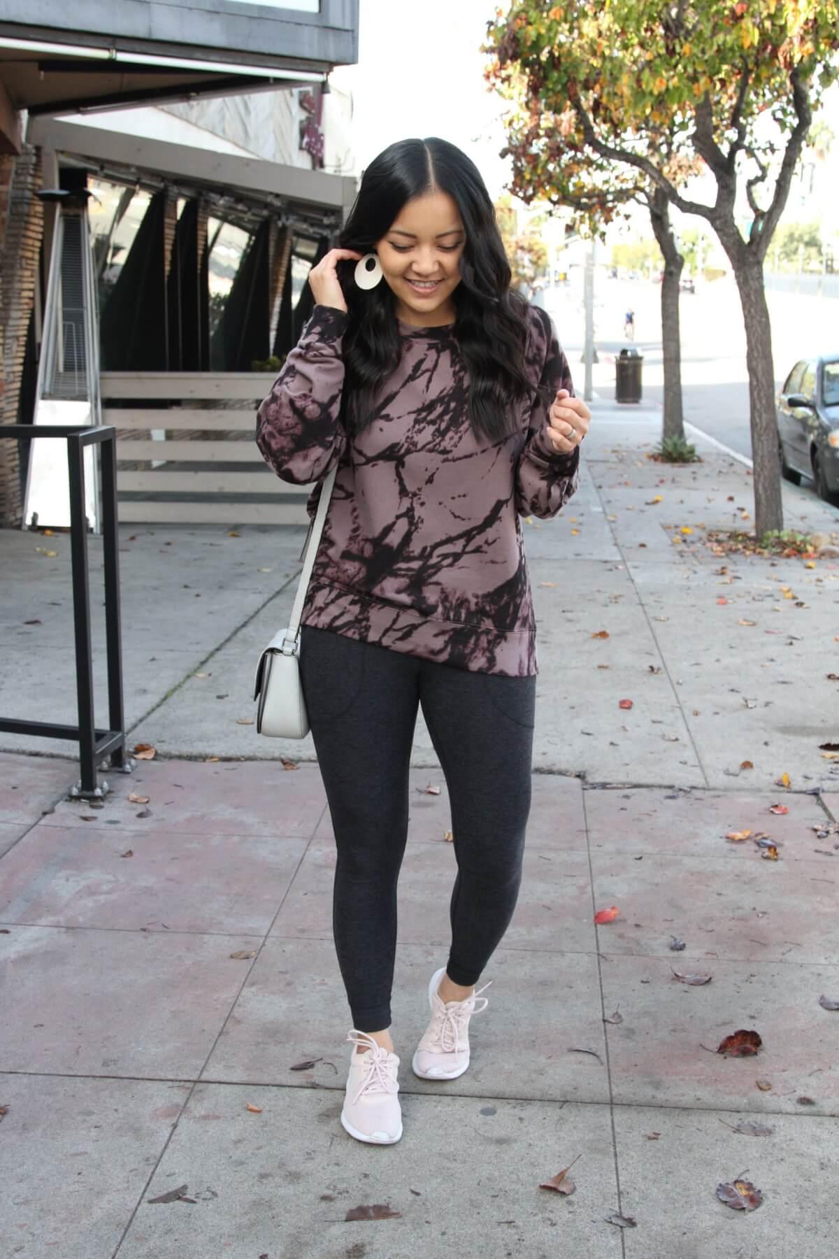 Winter Athleisure Outfit: purple and black splattered sweatshirt + dark grey pocket leggings + blush sneakers + grey crossbody bag + cream leather earrings