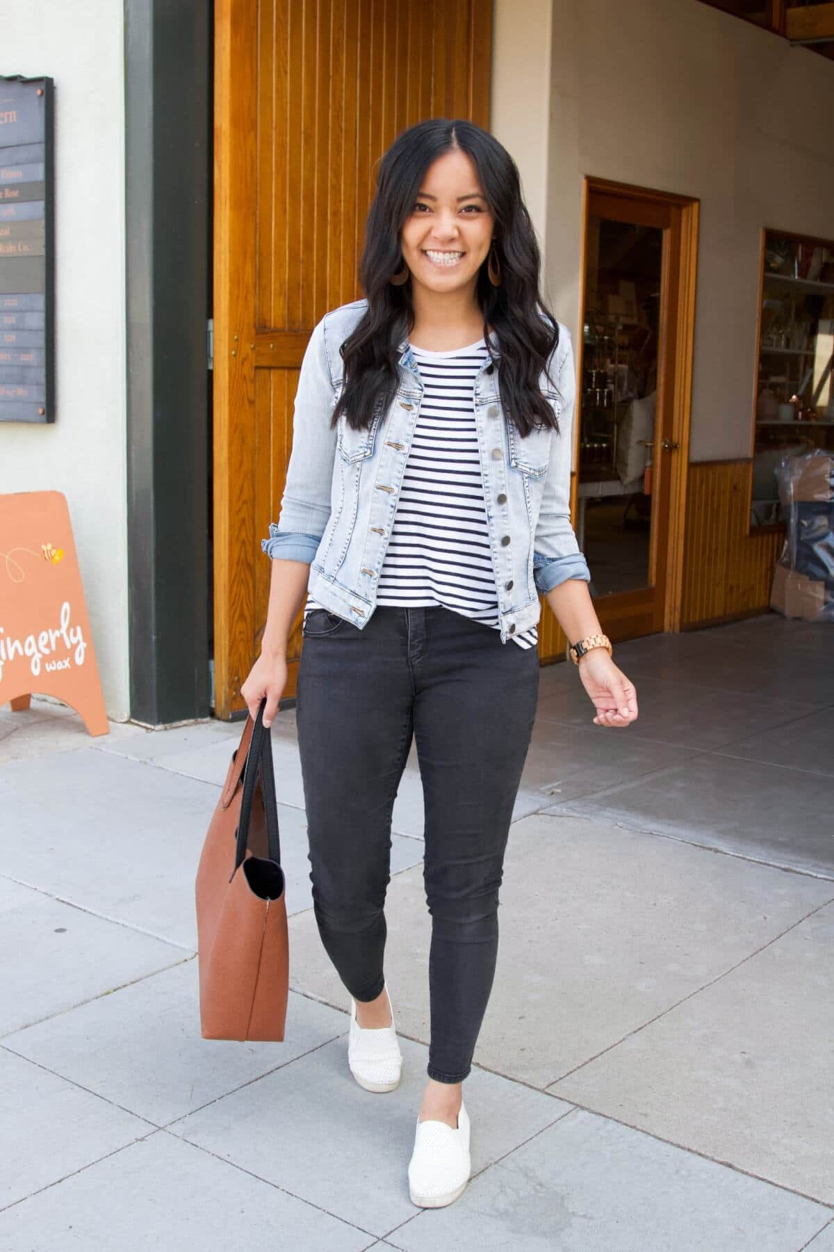 Casual Black Jeans Outfit: black and white striped tee + denim jacket + black skinny jeans + white slip-on sneakers + cognac tote + cognac leather earrings