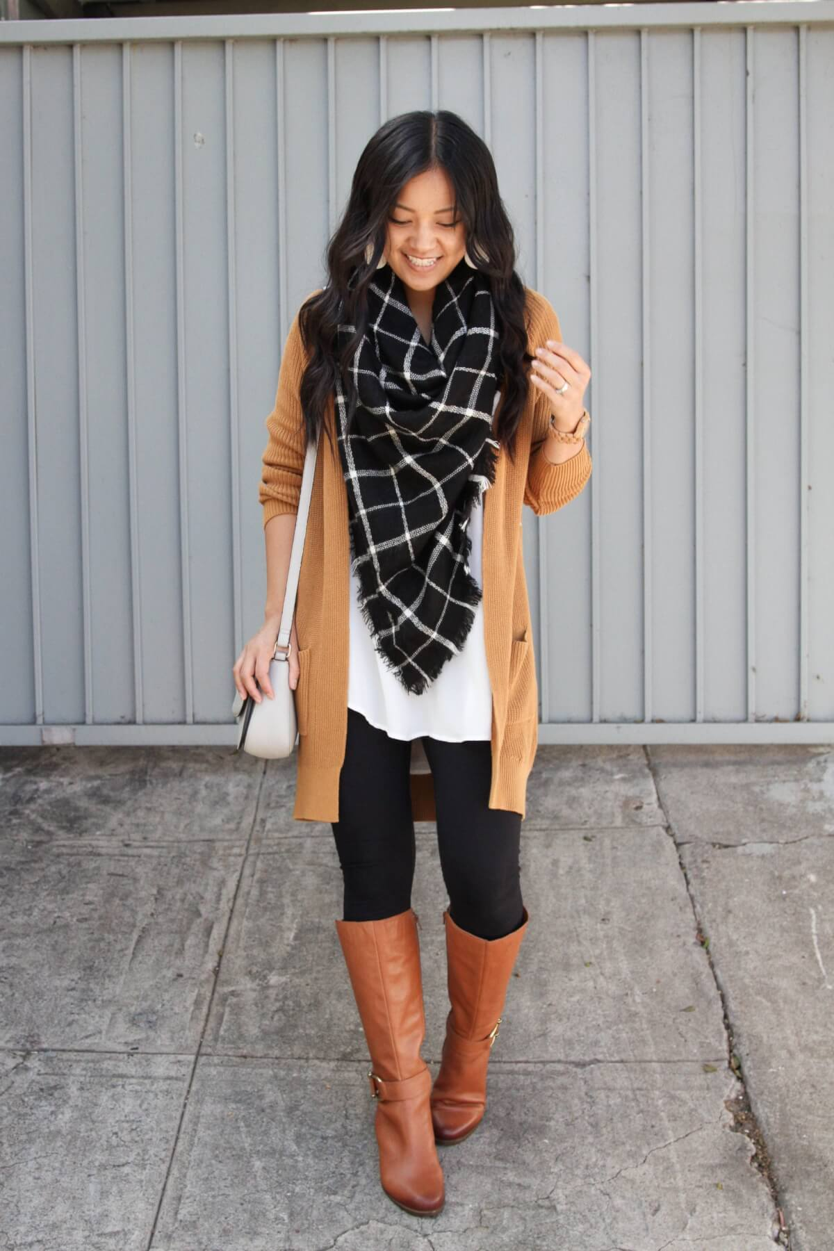 Winter Leggings Outfit: white tunic + tan cardigan + black and white plaid blanket scarf + black leggings + cognac leather boots + grey crossbody bag + metallic leather earrings