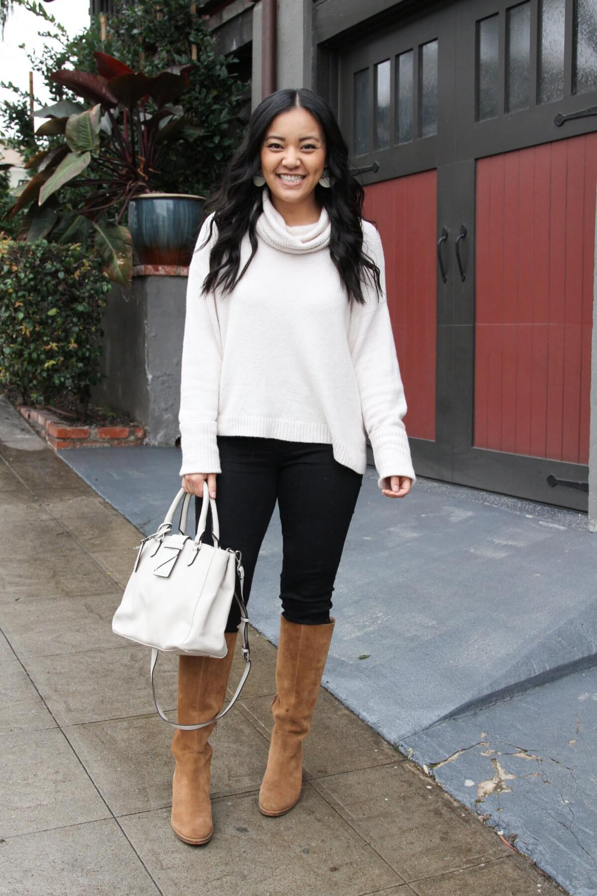winter outfit: white turtleneck sweater + black jeans + cognac boots + white handbag