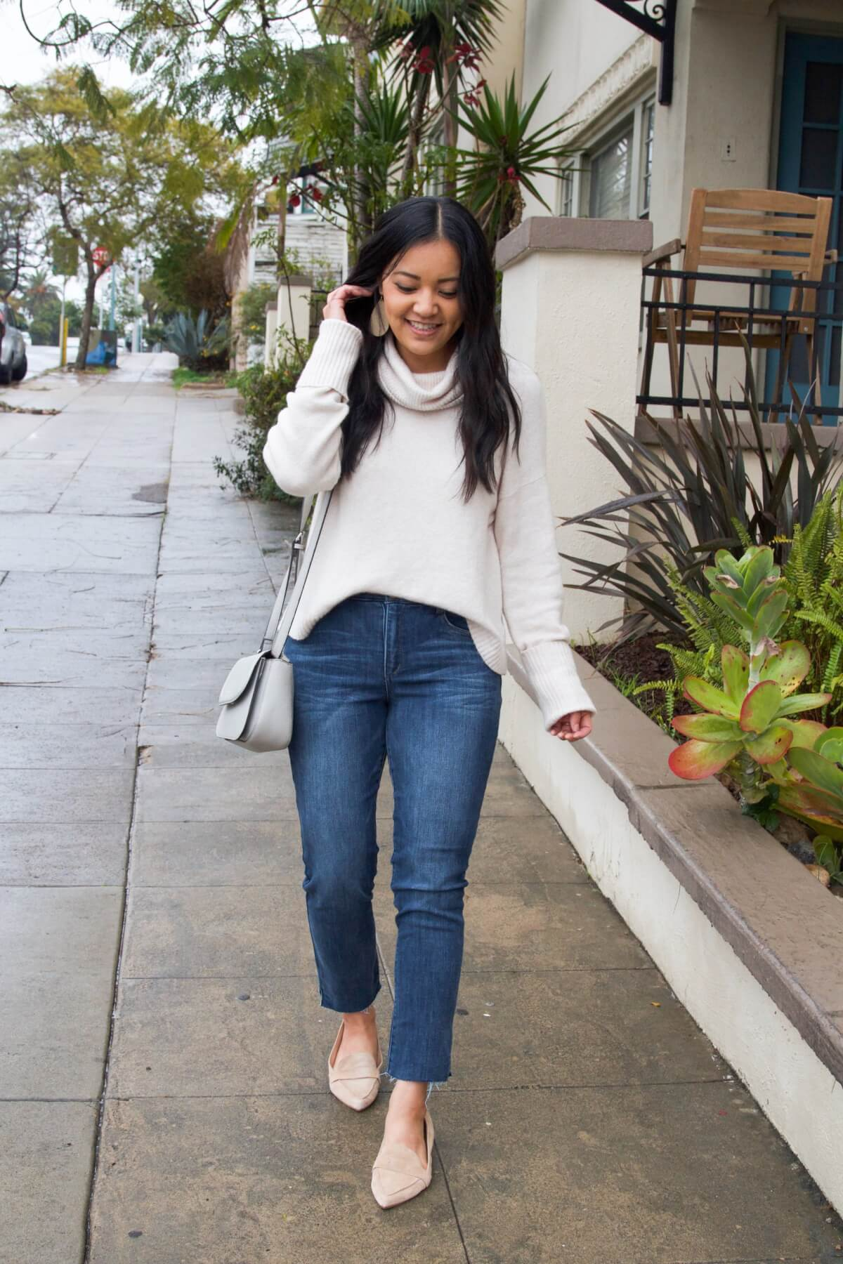spring outfit: white turtleneck sweater + blue cropped jeans + neutral flats + gray purse + white leather earrings