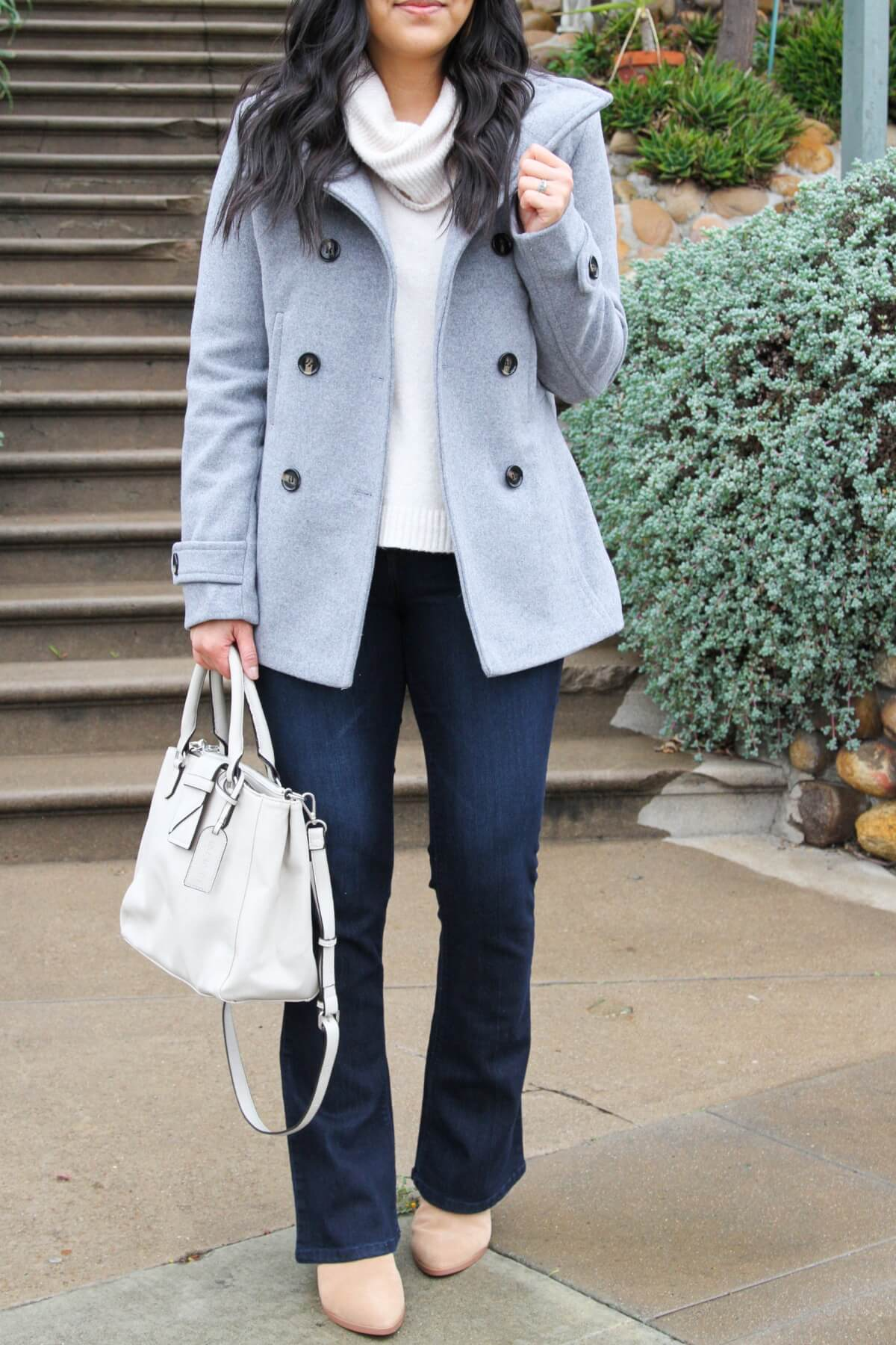 winter outfit close up: white turtleneck sweater + gray peacoat + blue jeans + white handbag