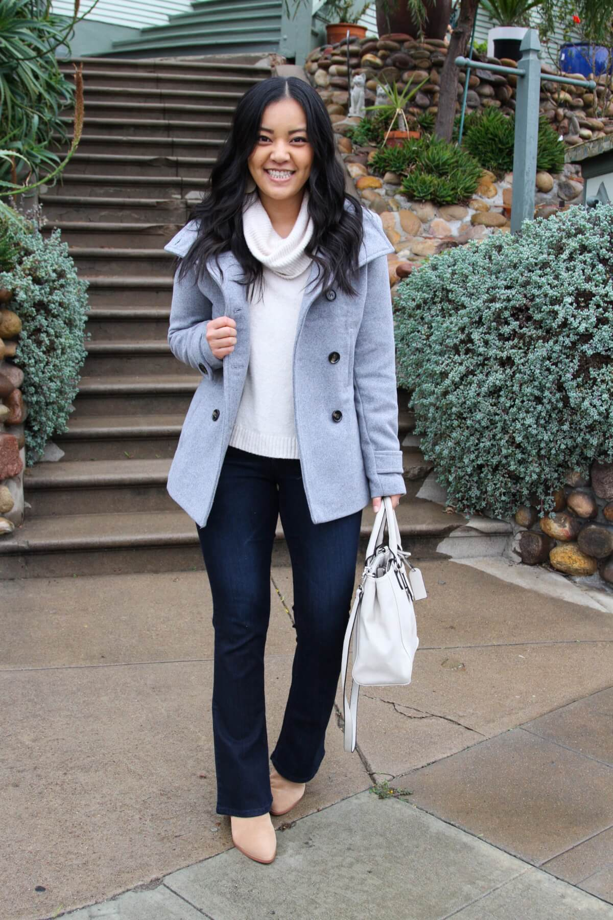 winter outfit: white turtleneck sweater + gray peacoat + bootcut jeans + neutral boots + white handbag