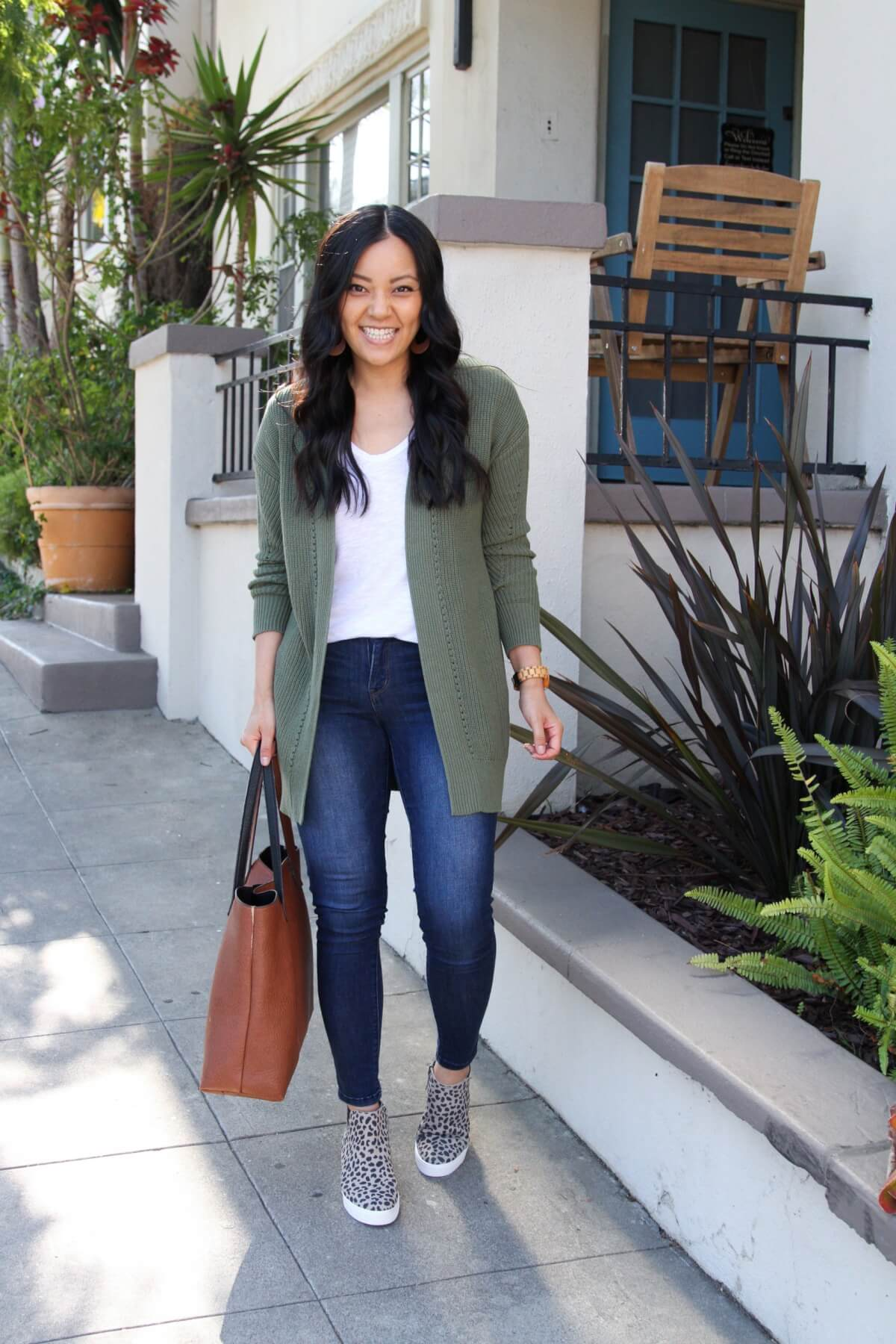 long cardigan outfit: green sweater + white tee + jeans + leopard slip-ons + cognac tote