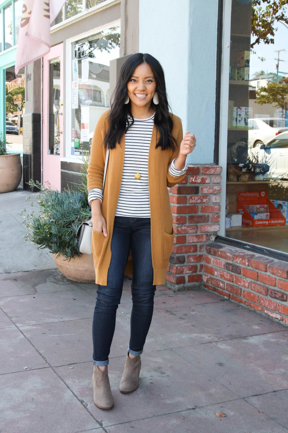 long cardigan outfit: mustard cardigan + striped tee + jeans + ankle boots + long necklace + gray purse