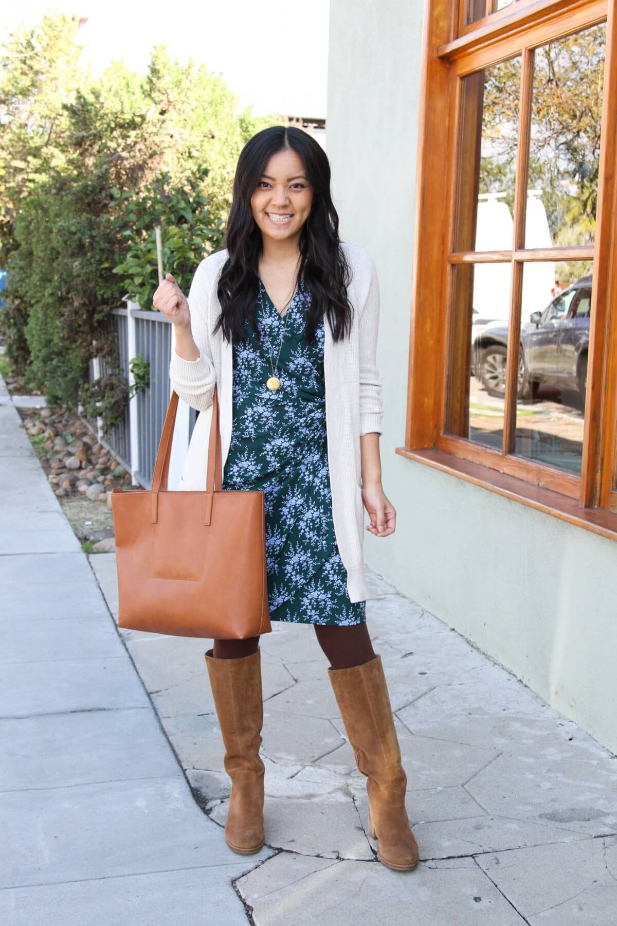 long cardigan outfit: white cardigan + blue floral dress + maroon tights + tall boots + gold necklace + cognac tote