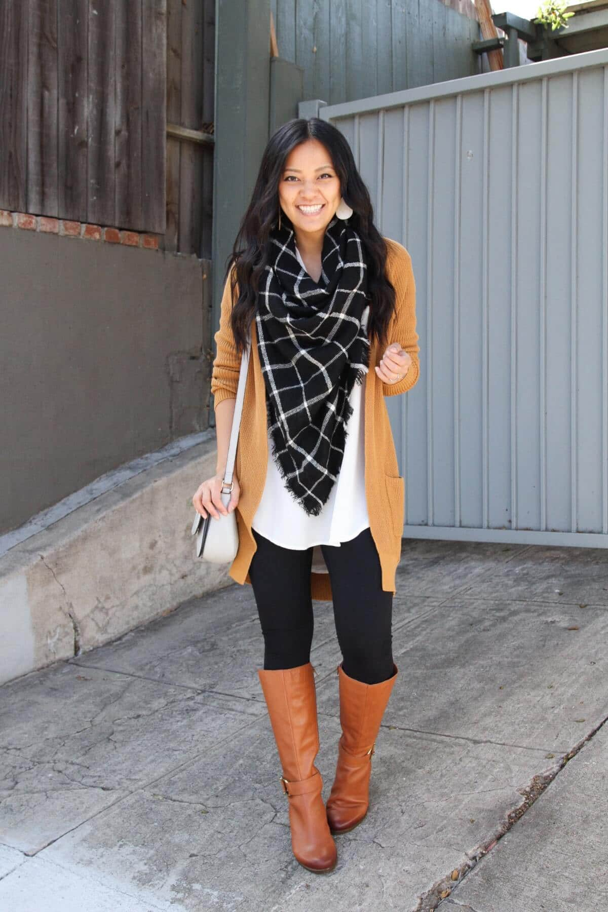 long cardigan outfit: mustard cardigan + black and white blanket scarf + white tunic + black leggings + cognac boots + gray purse