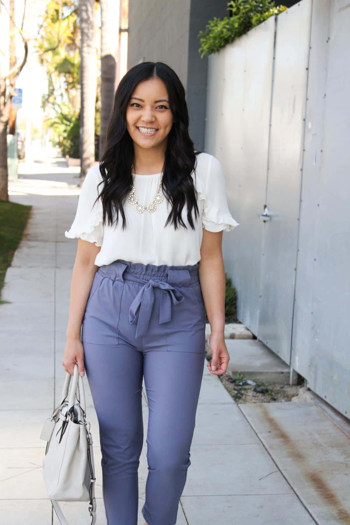 white top for spring: white top, blue paper bag tie-waist pants, statement necklace, white bag