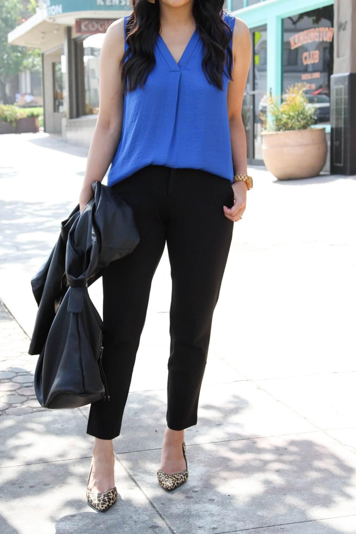 comfy work outfit for spring: blue top, black slacks, black bag, leopard heels, black moto jacket
