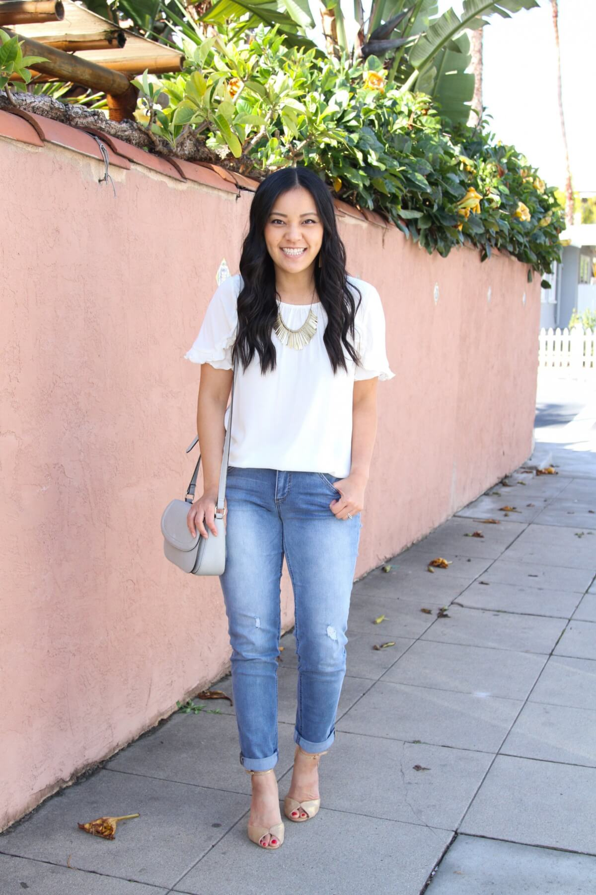 Classic Outfit: white ruffle sleeve top + distressed jeans + metallic heels + metallic statement necklace + gray bag