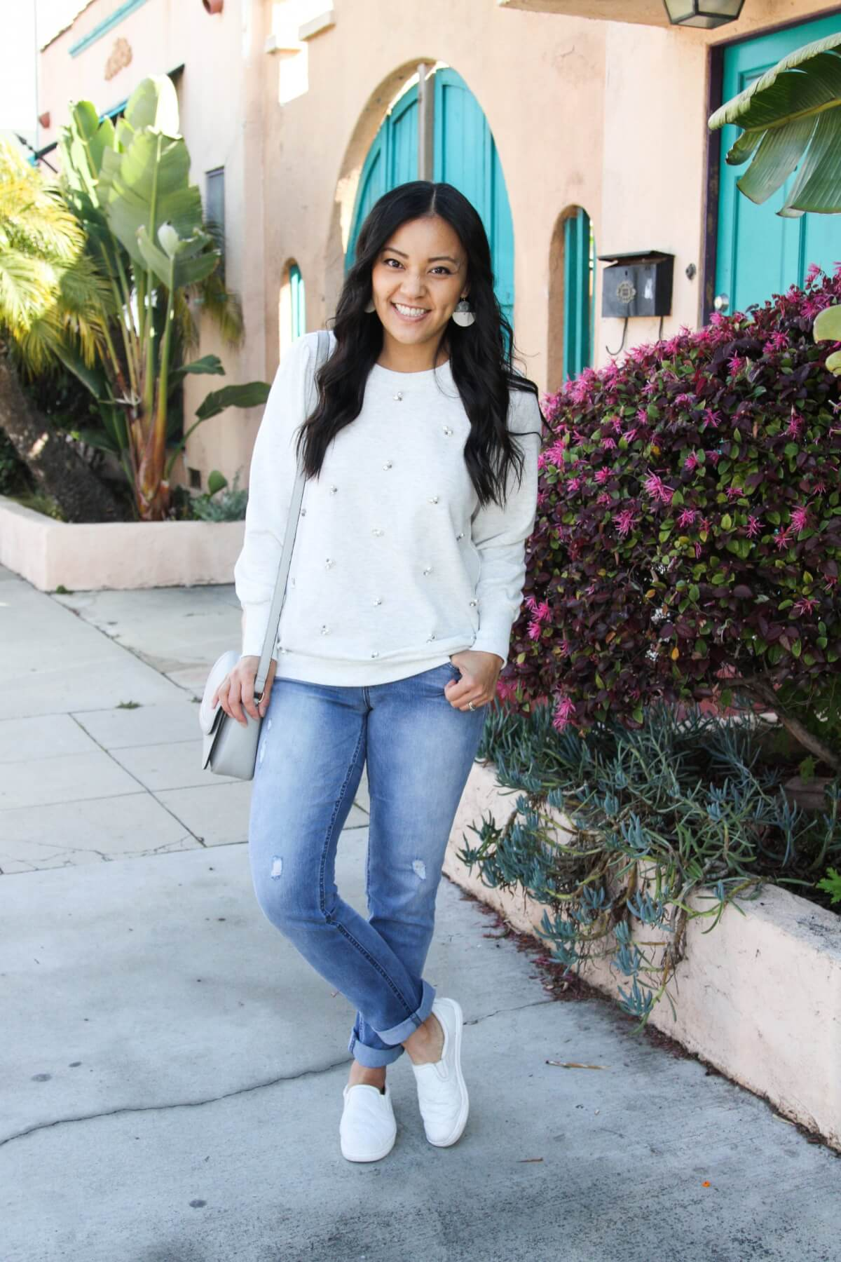 casual spring outfit: embellished sweatshirt, girlfriend jeans, white slip-on sneakers, gray purse