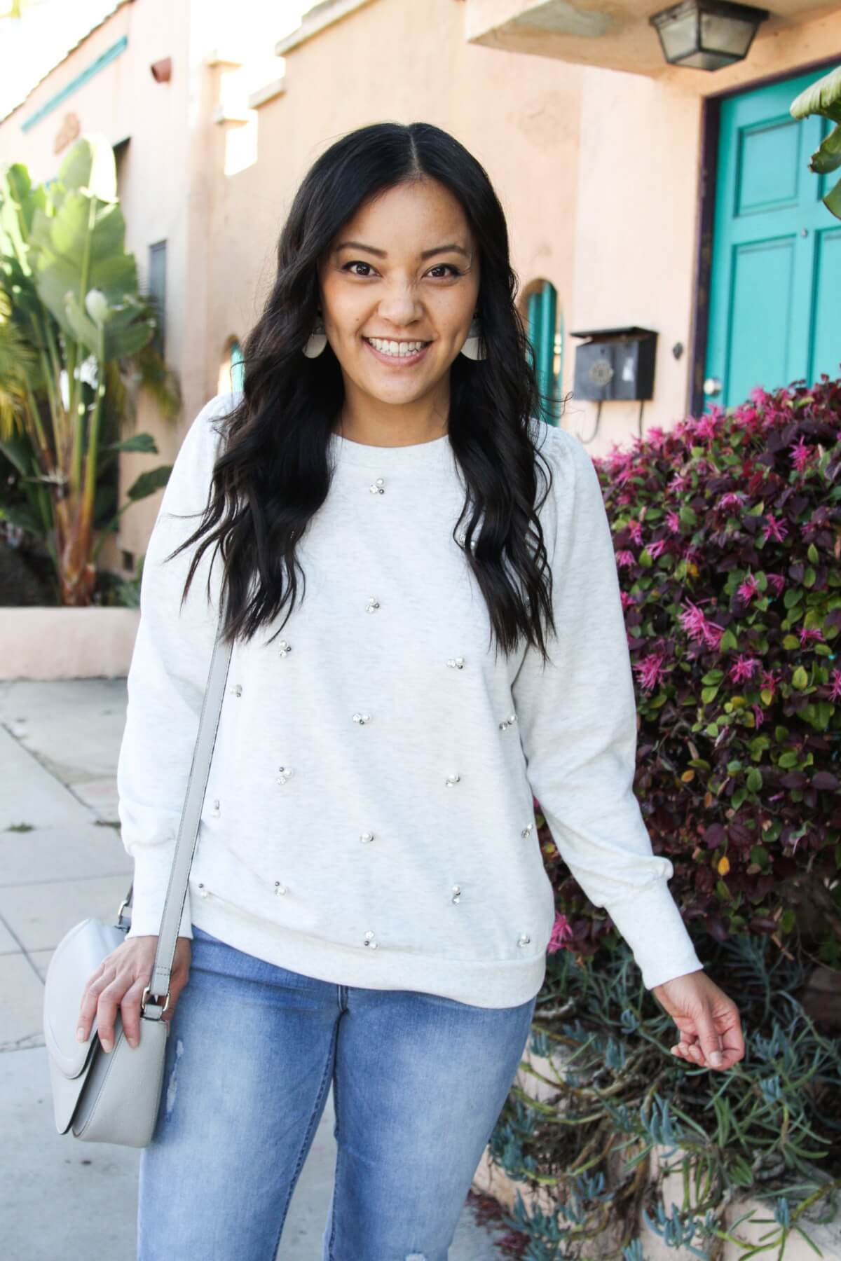 casual spring outfit: embellished sweatshirt, girlfriend jeans, gray purse, white earrings