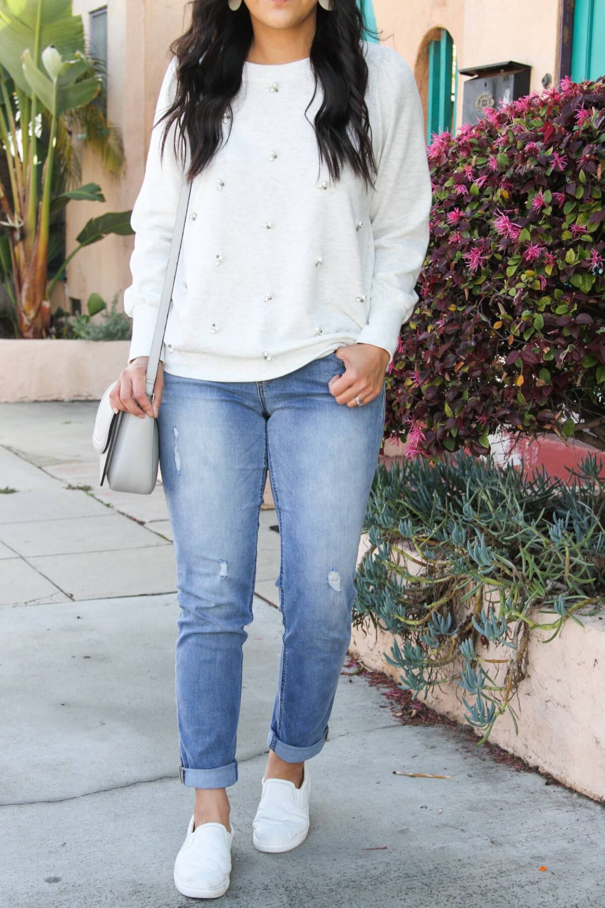 casual spring outfit: embellished sweatshirt, girlfriend jeans, white slip-on sneakers, gray purse, white earrings, close up