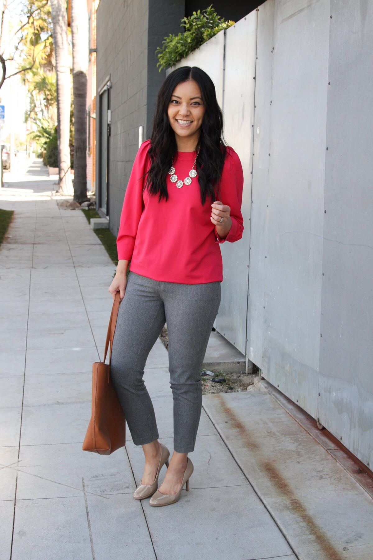 spring business casual outfit: colorful top + neutral pants + statement necklace + nude pumps + brown tote