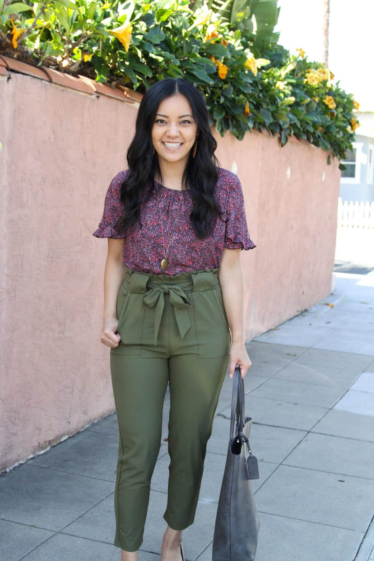 spring business casual outfit: printed blouse + olive paper bag tie waist pants + pendant necklace + grey tote close-up
