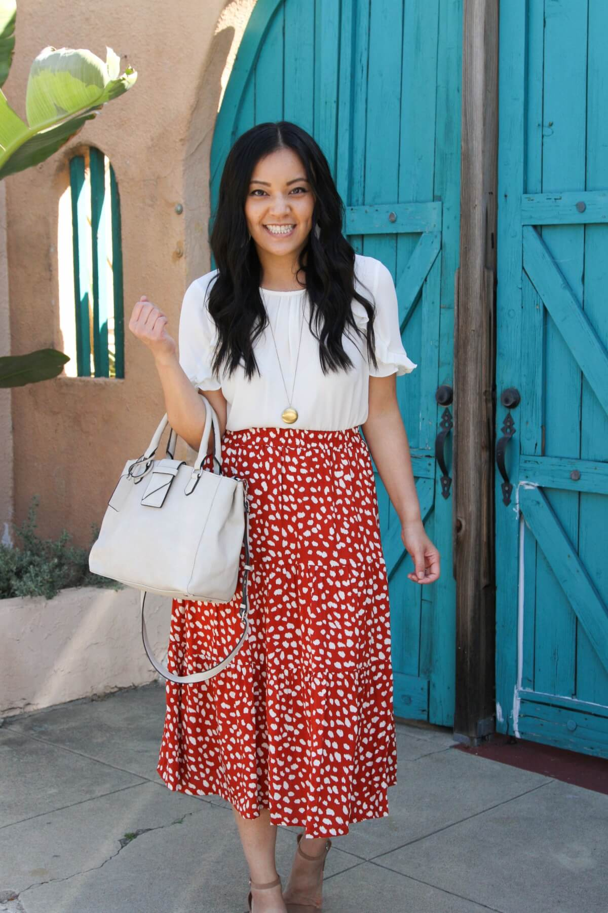 spring business casual outfit: white blouse + printed skirt + nude sandals + pendant necklace + white bag