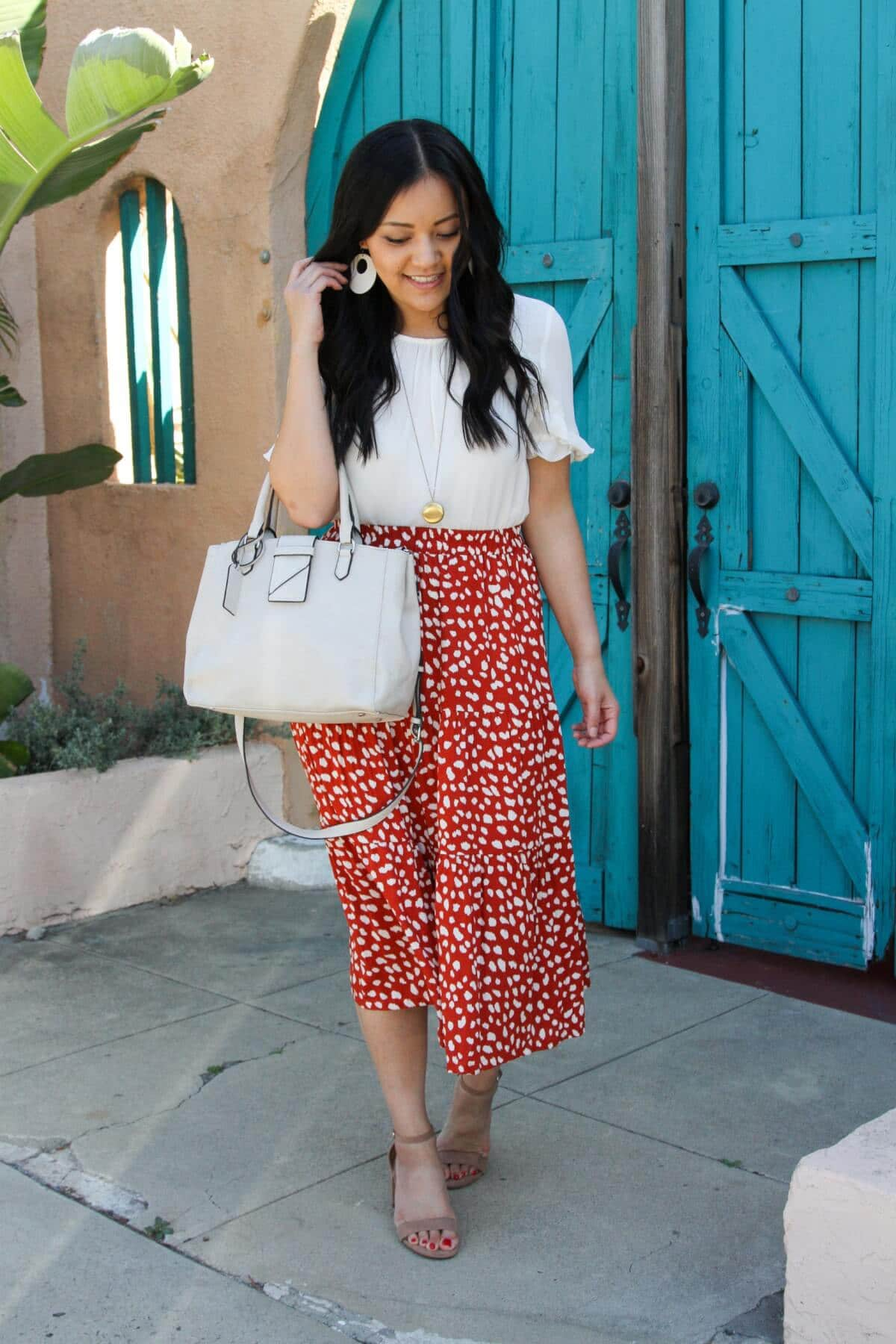 spring business casual outfit: white blouse + red printed skirt + nude sandals + pendant necklace + white bag