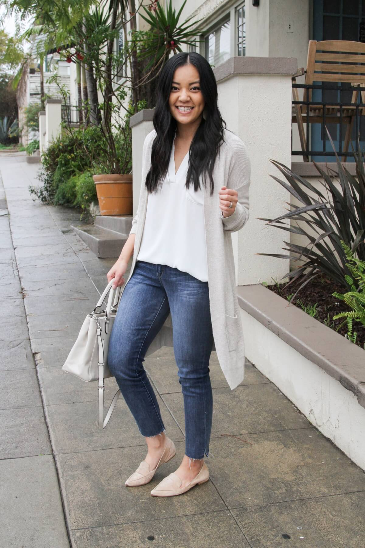 comfy elevated casual outfit for spring: white tunic, light cardigan, jeans, nude flats, white bag, side view