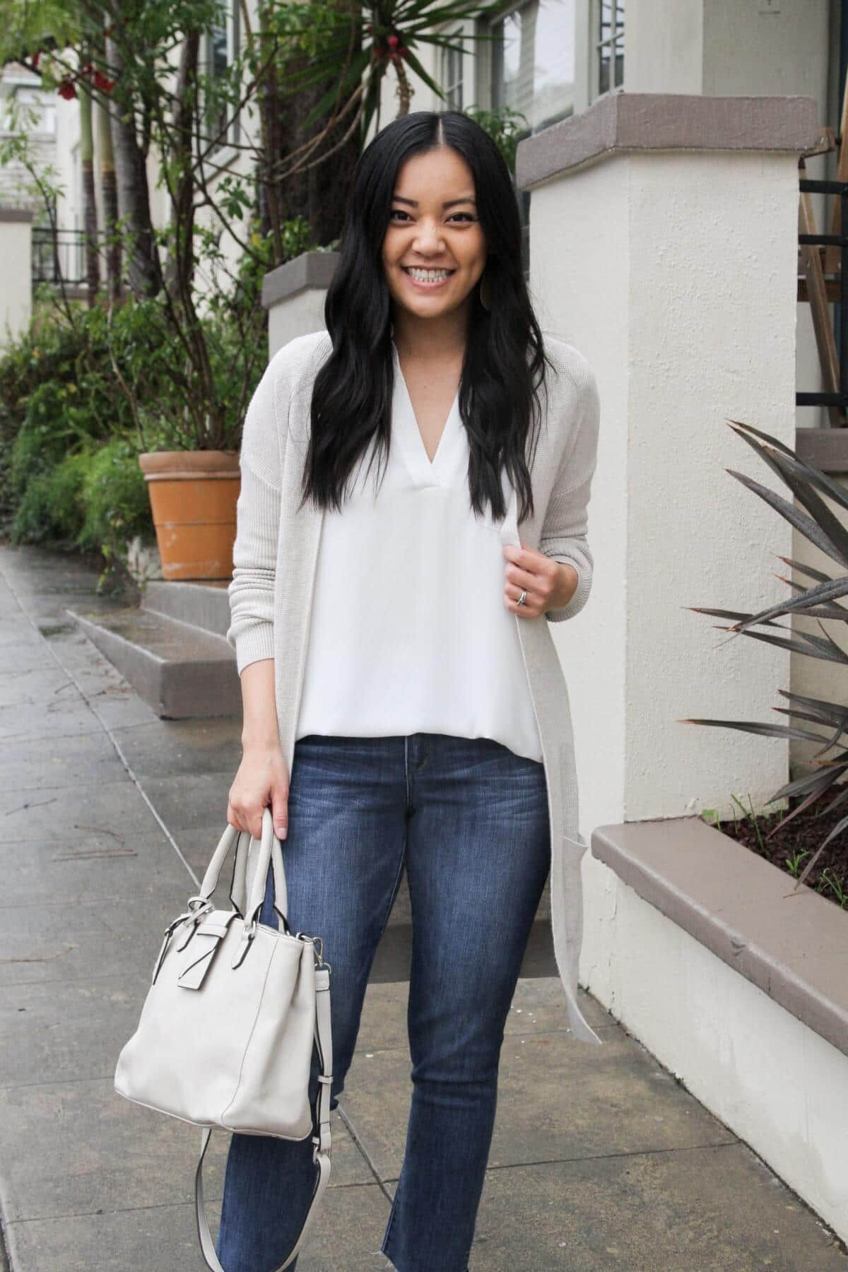 comfy elevated casual outfit for spring: white tunic, light cardigan, jeans, white bag