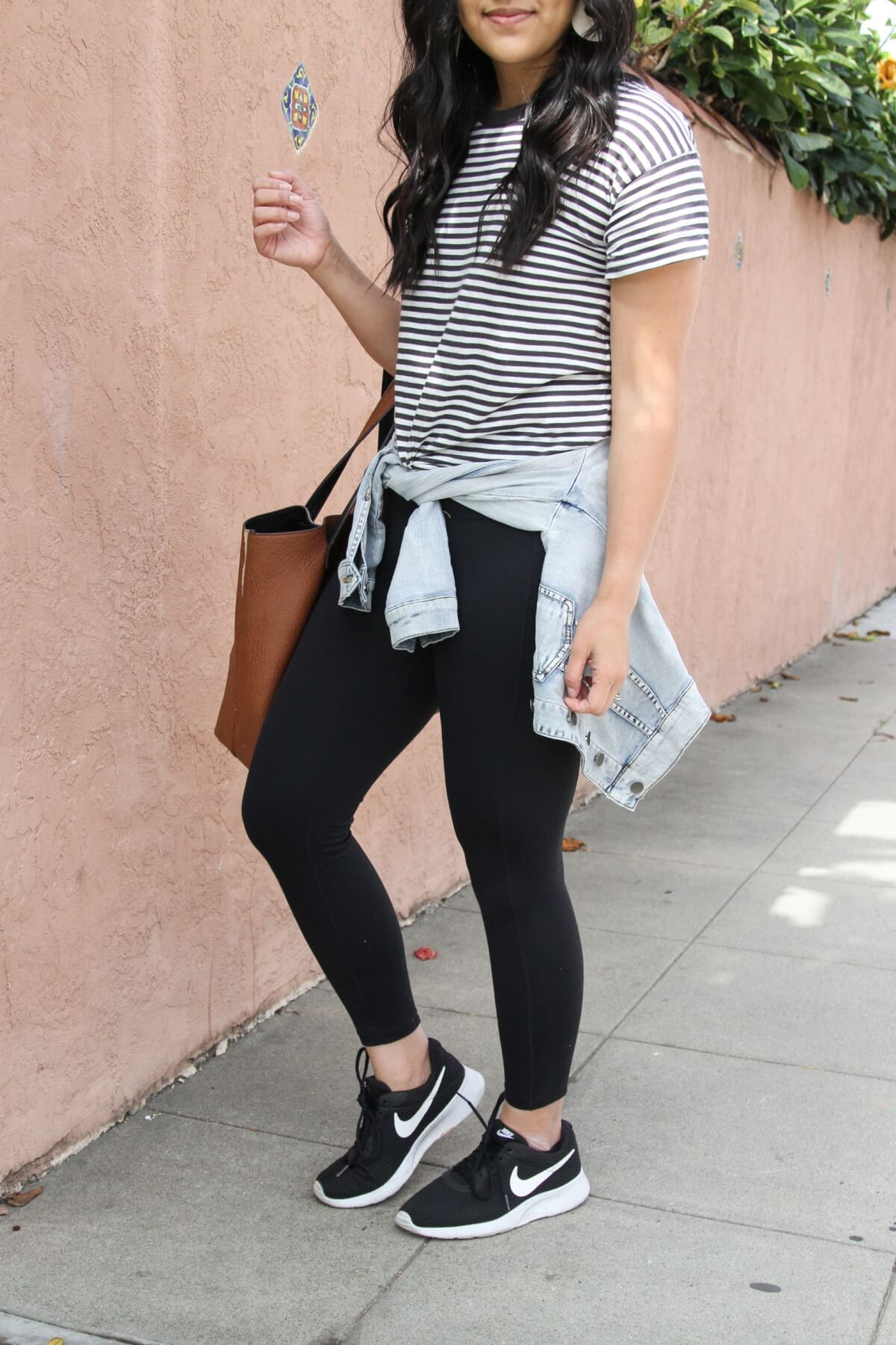 Easy to Wear Shoes for Spring: black Nike tanjun sneakers + black and white striped tee + black leggings + denim jacket + white earrings + brown tote close up
