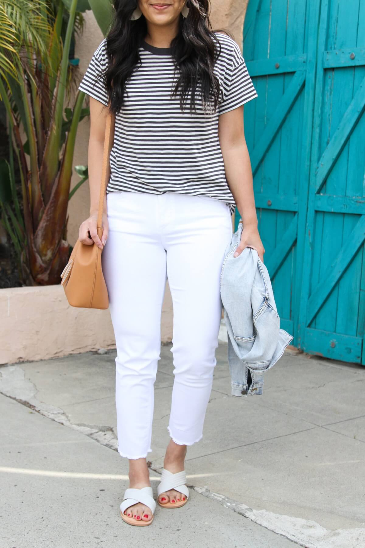 Easy to Wear Shoes for Spring: DV by Dolce Vita Lyra white slides + Madewell black and white striped tee + white straight leg jeans + denim jacket + white earrings + tan bag close up