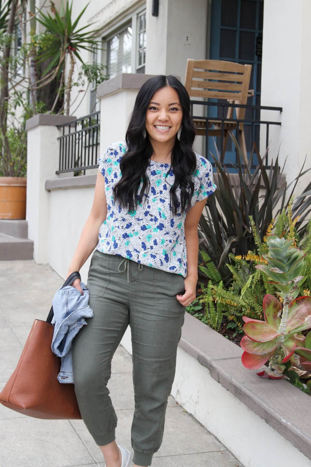 Casual Outfit: blue and green floral top + olive linen joggers + white slip-on sneakers + denim jacket + white earrings + brown tote