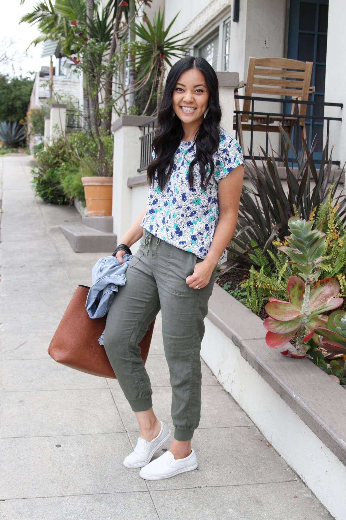 Casual Outfit: blue and green floral top + olive joggers + white sneakers + denim jacket + white earrings + brown tote